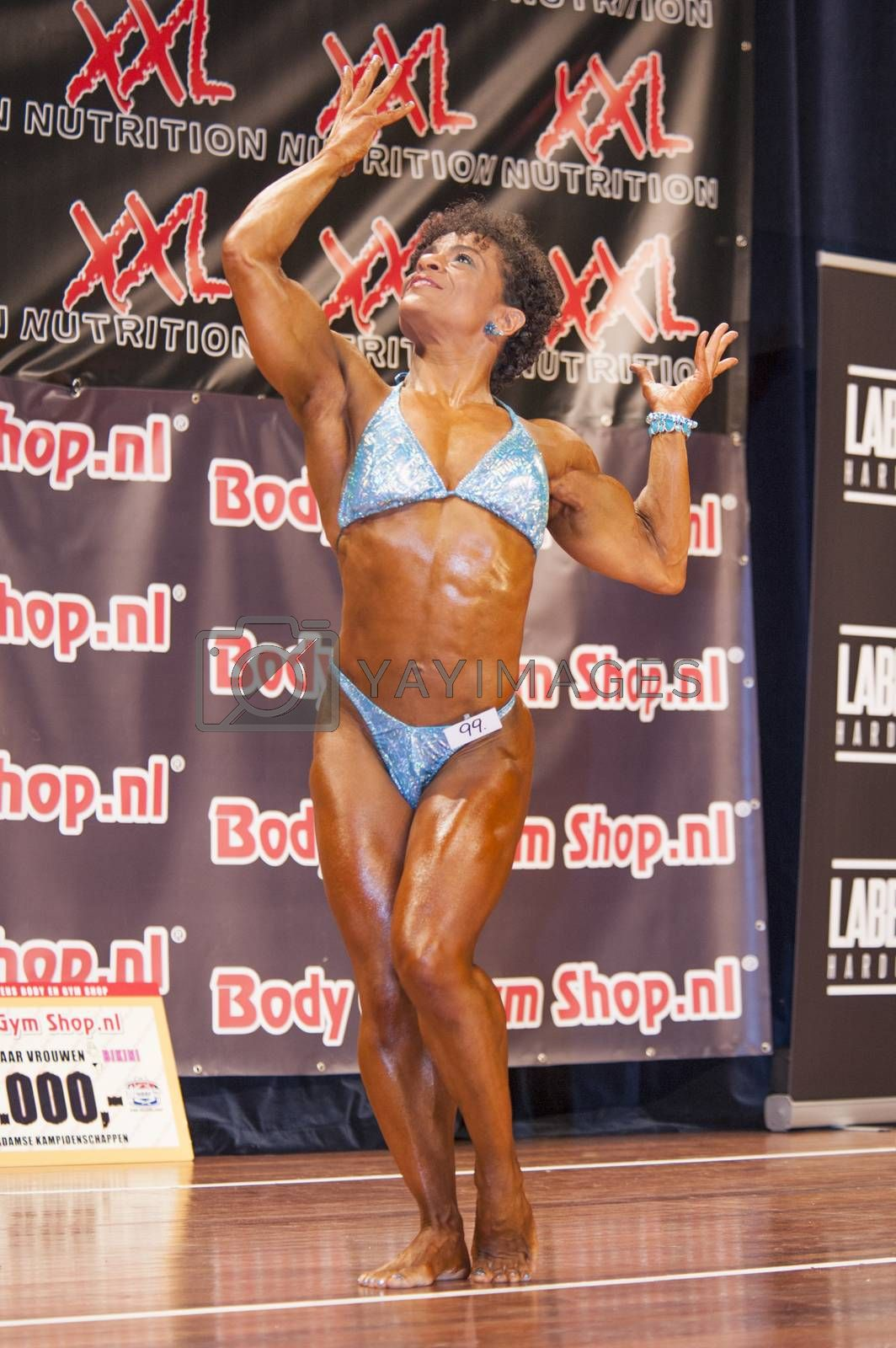Female bodybuilder shows het muscles on stage by yellowpaul