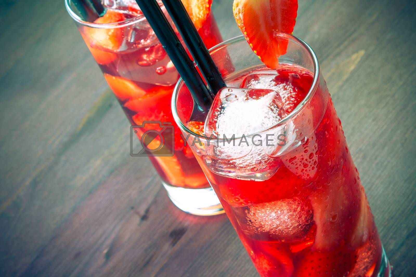 top of view of two glasses of strawberry cocktail with ice by donfiore