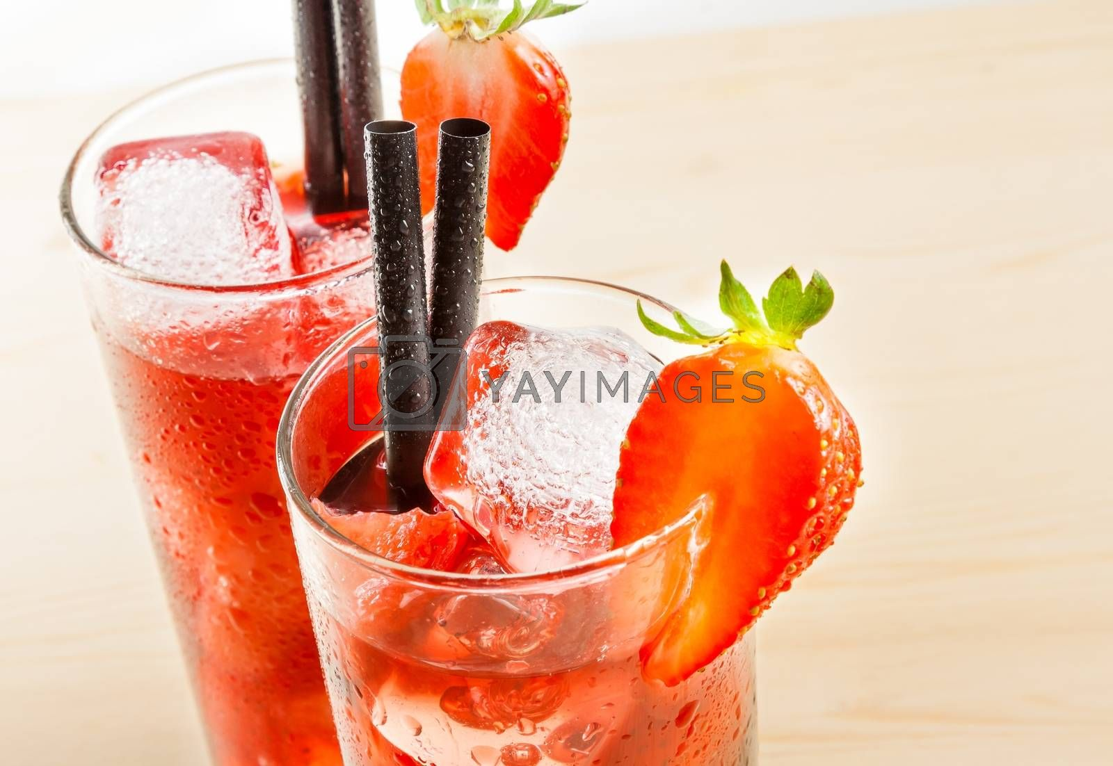 detail of two glasses of strawberry cocktail with ice on light wood table  by donfiore
