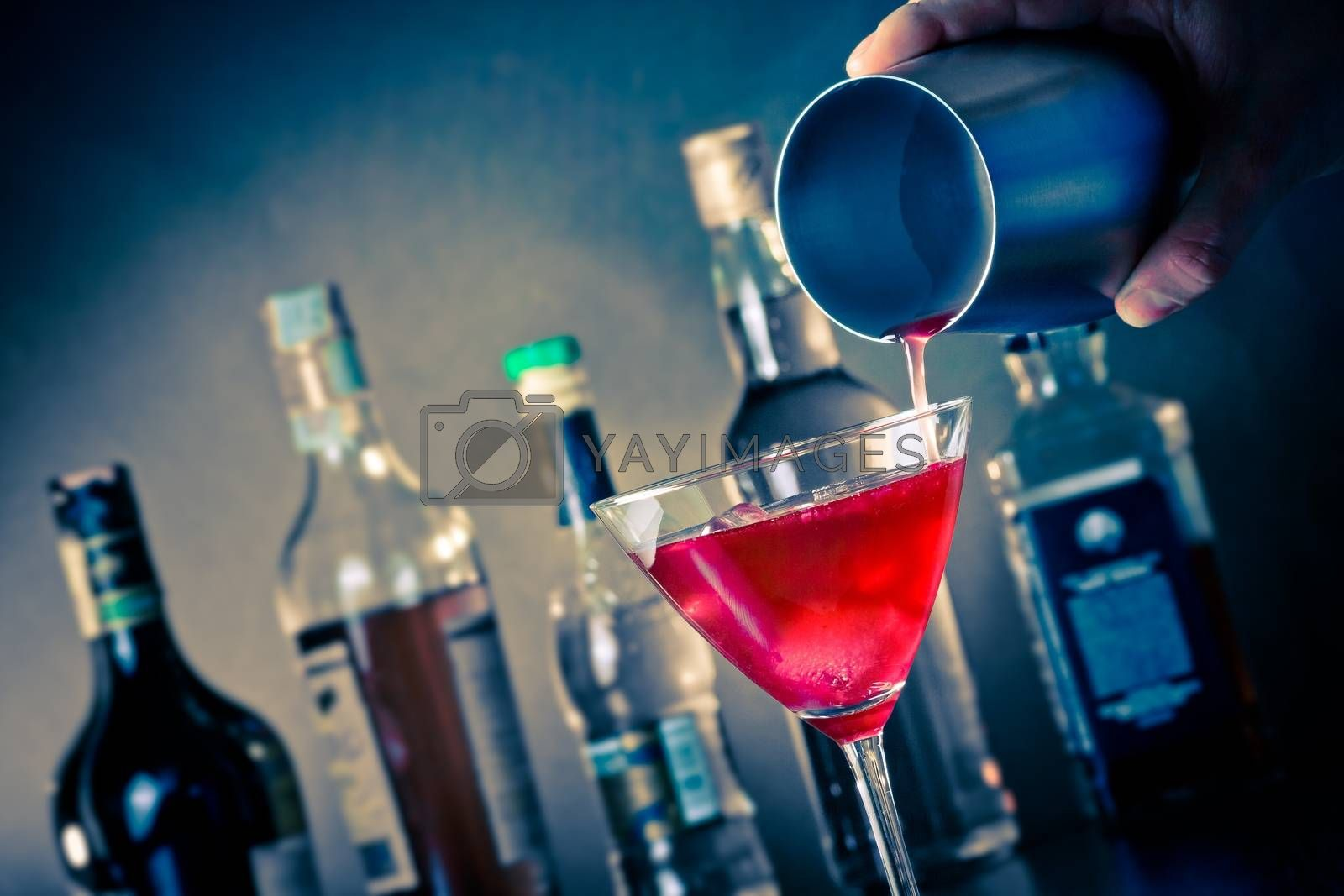 Barman pouring a red cocktail into a glass with ice by donfiore