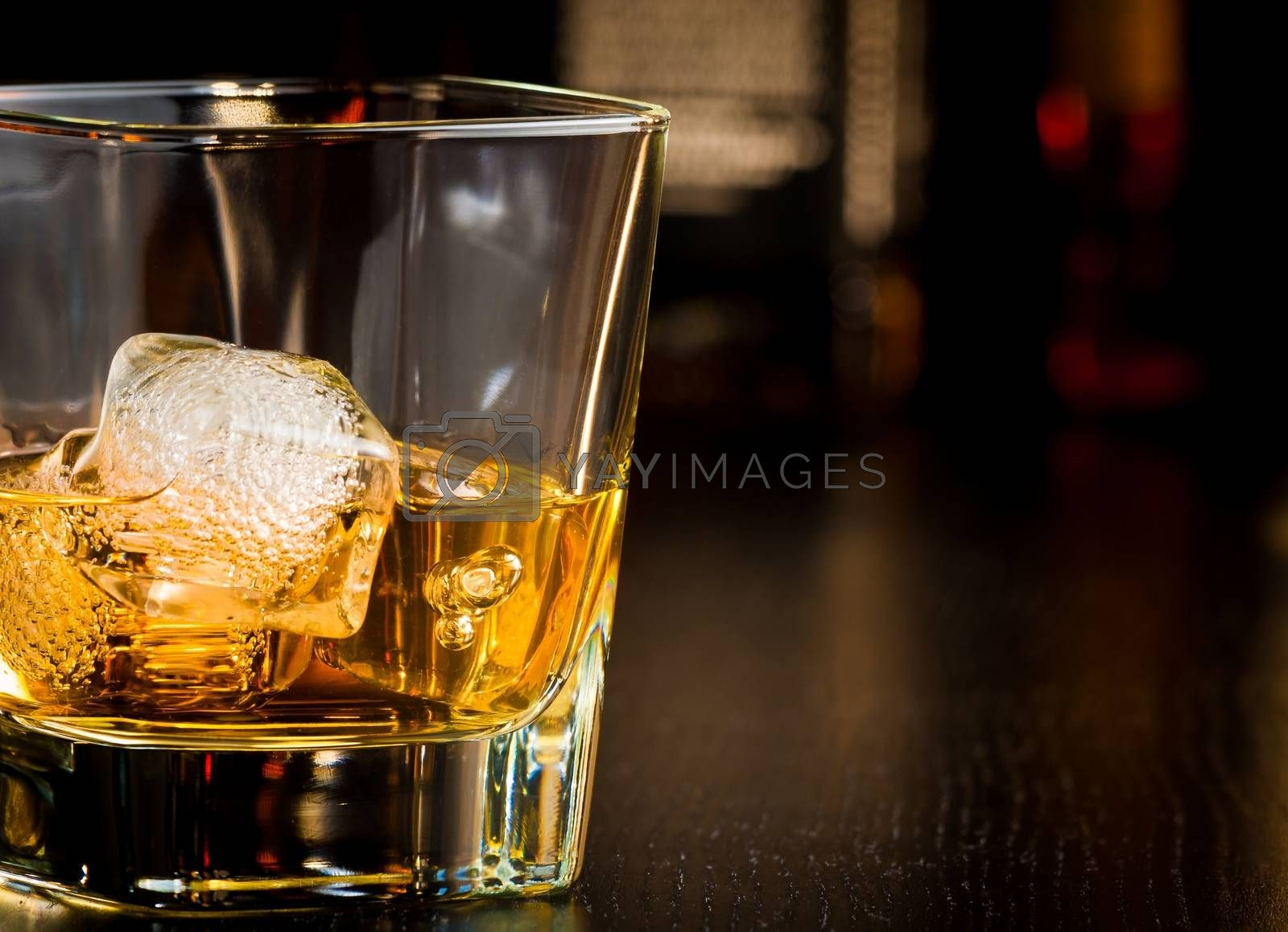 whiskey glass with ice in front of bottles with space for text by donfiore