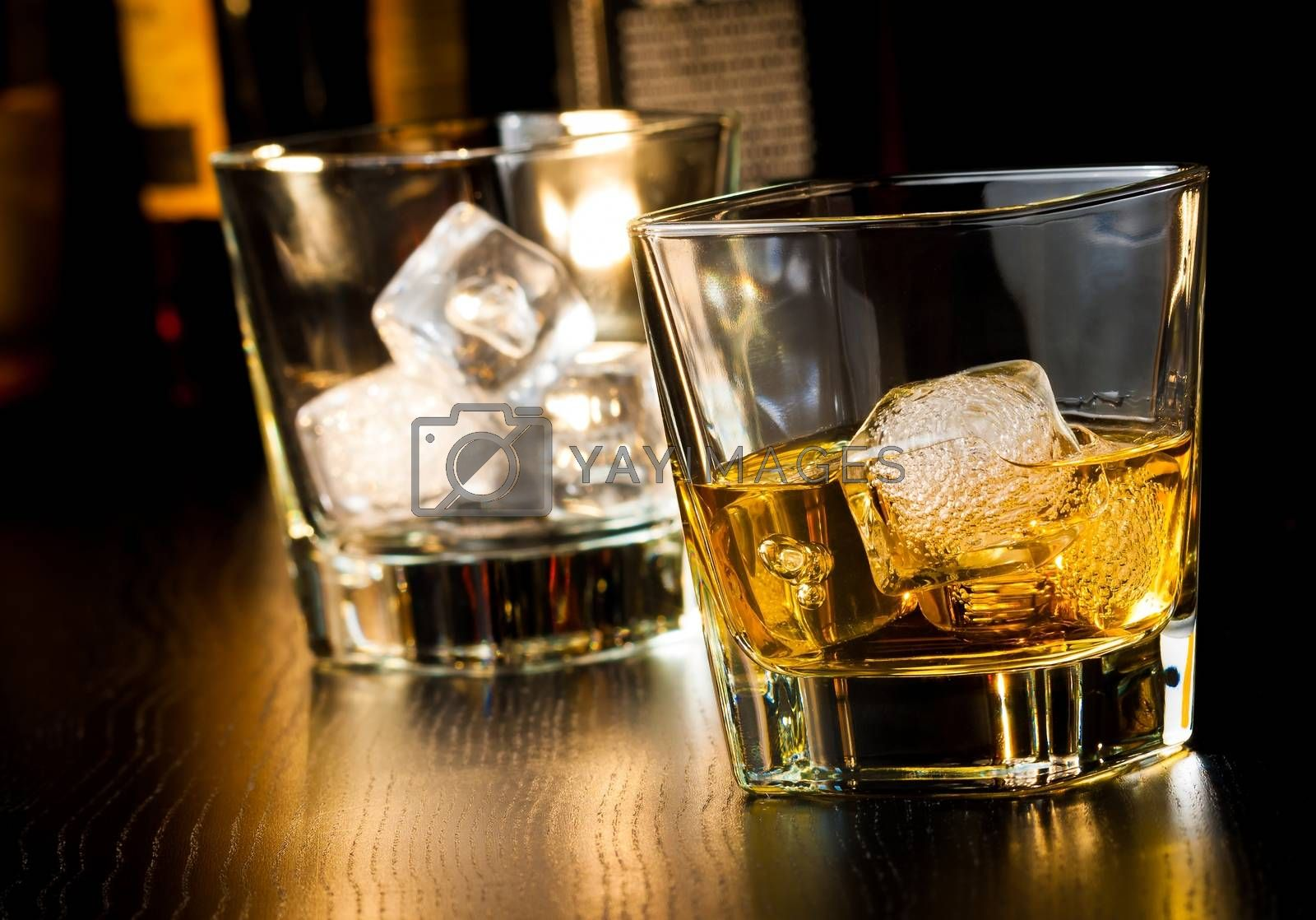 whiskey glass with ice in front of empty whiskey glass  by donfiore