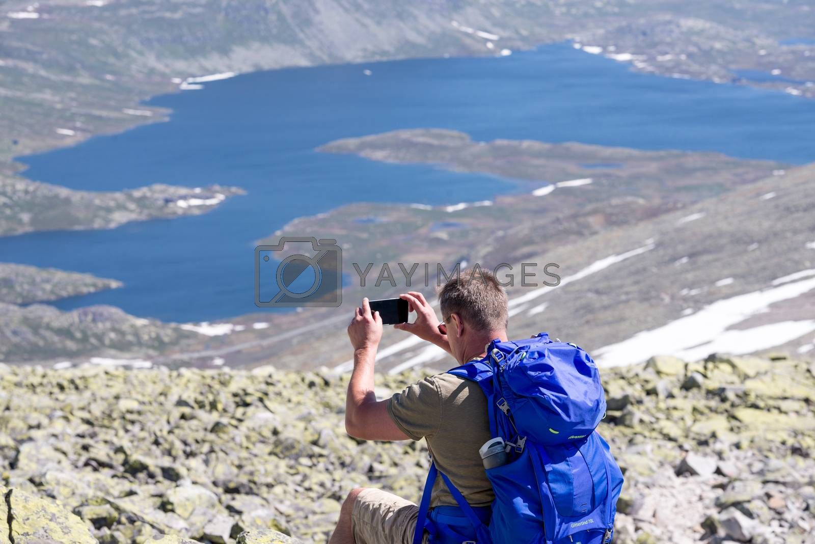 Hiker with big traveling rucksack taking pictures on the phone by Nanisimova