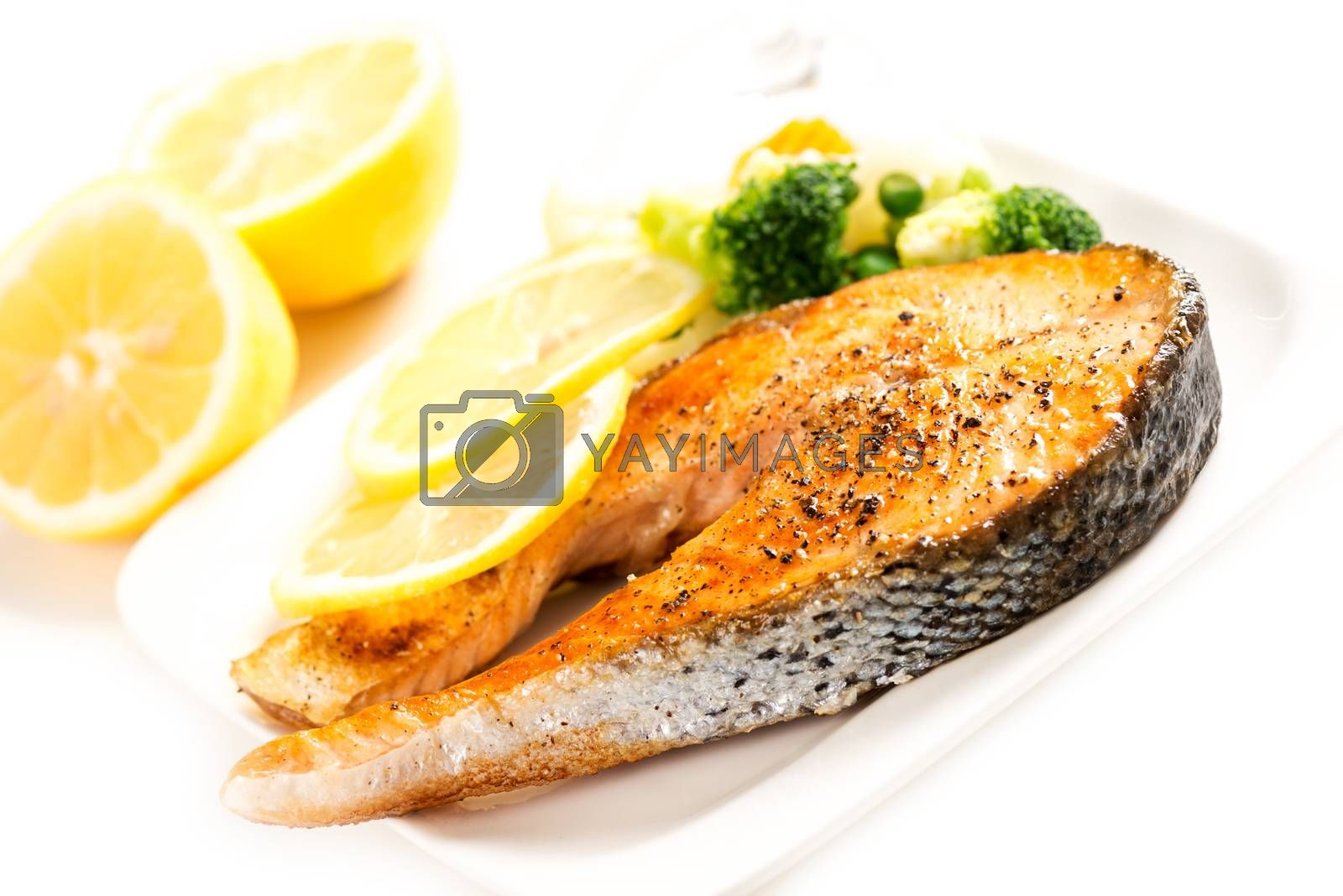 Grilled salmon and vegetables on plate with lemon by Nanisimova