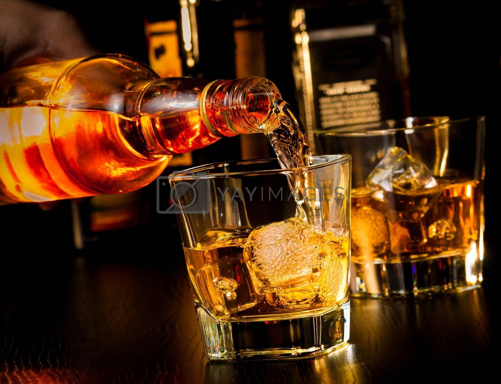 barman pouring whiskey in front of whiskey glass and bottles by donfiore