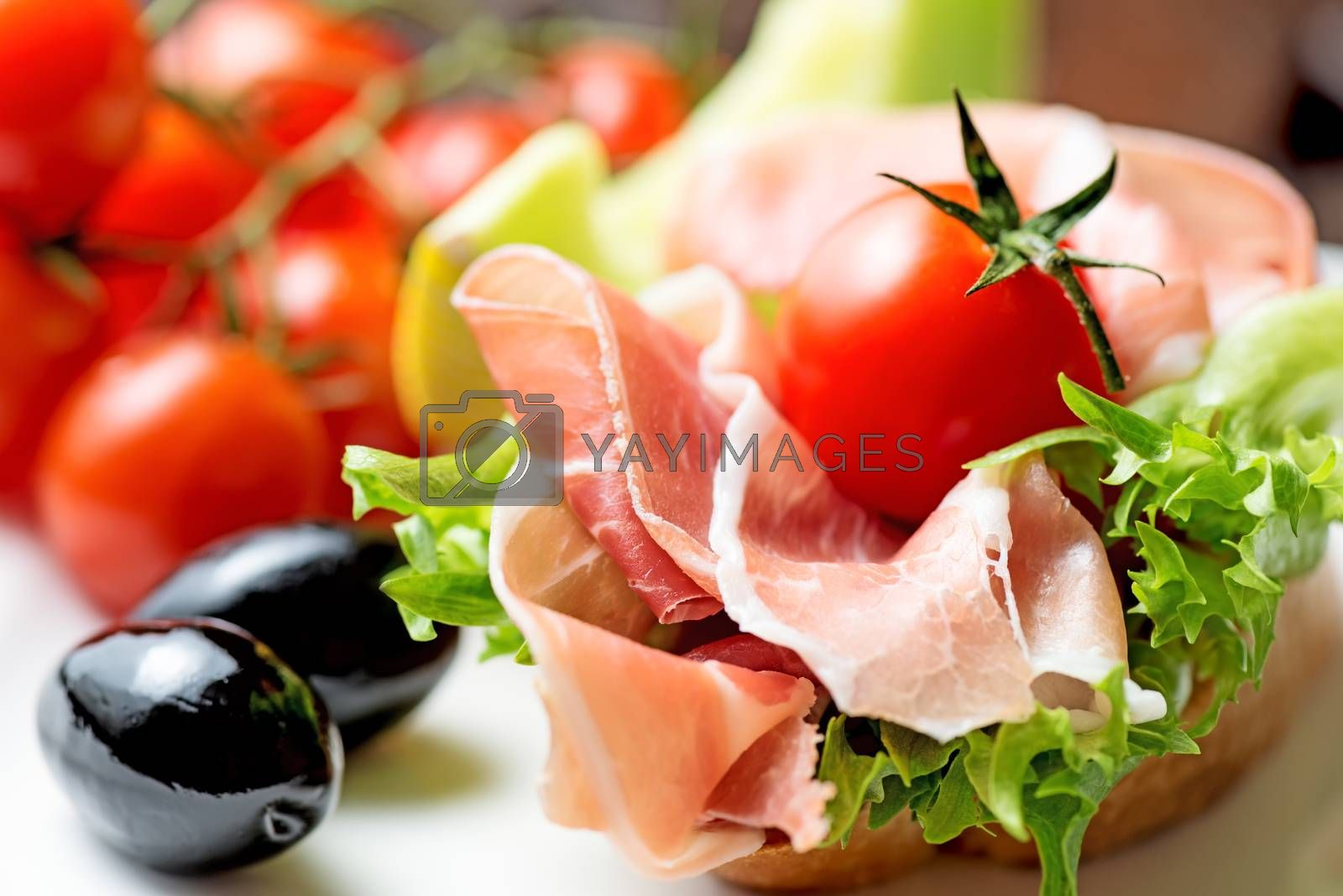 thin slices of prosciutto with olives and tomato on plate close  by Nanisimova