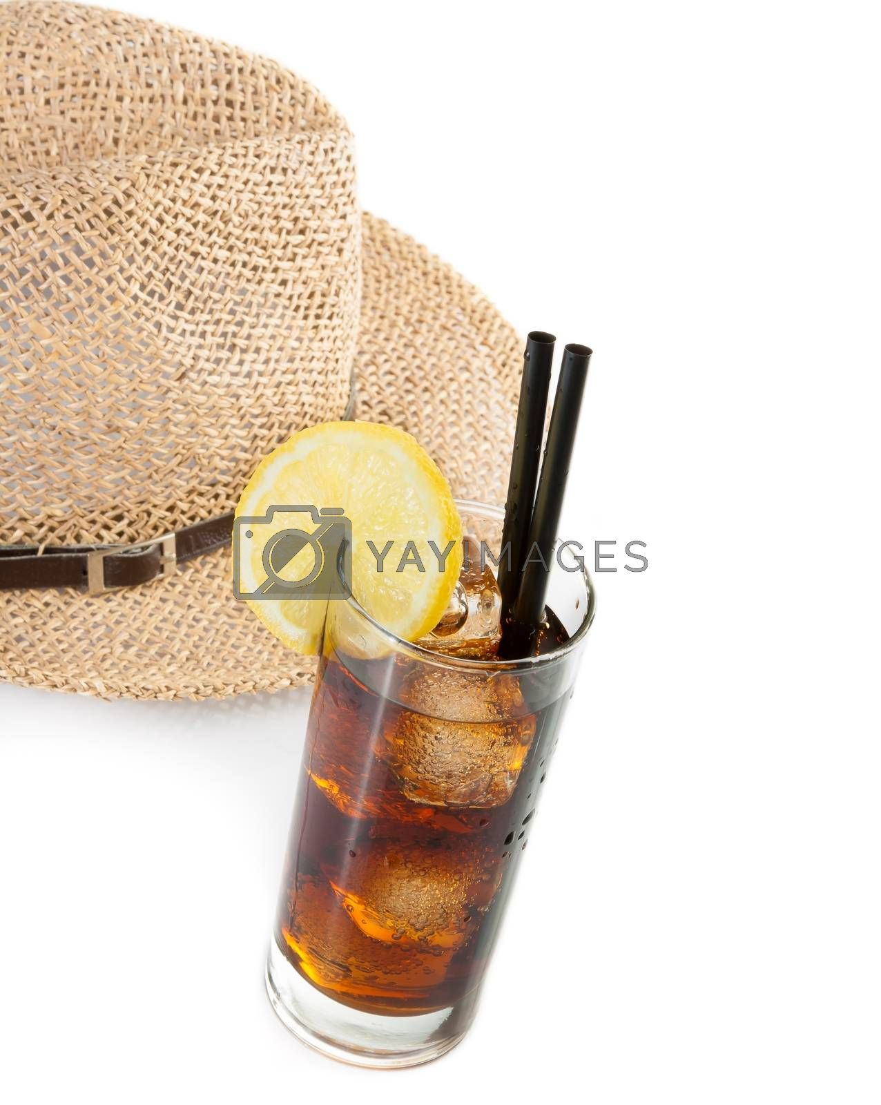 glass of fresh coke with straw in front of summer hat, summer time by donfiore