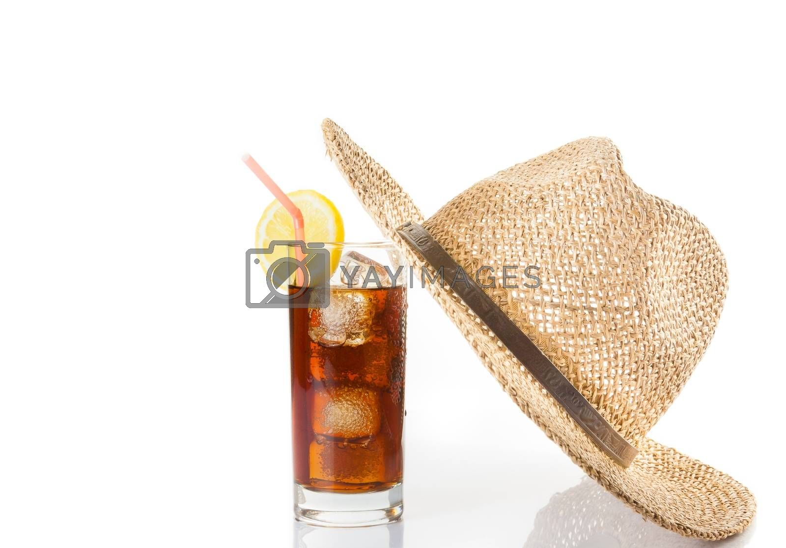 glass of fresh coke with straw near summer hat on top, summer time by donfiore