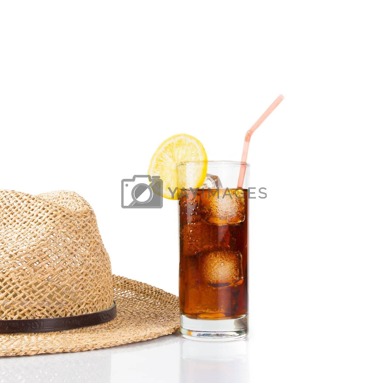 glass of fresh coke with straw near summer hat, summer time by donfiore