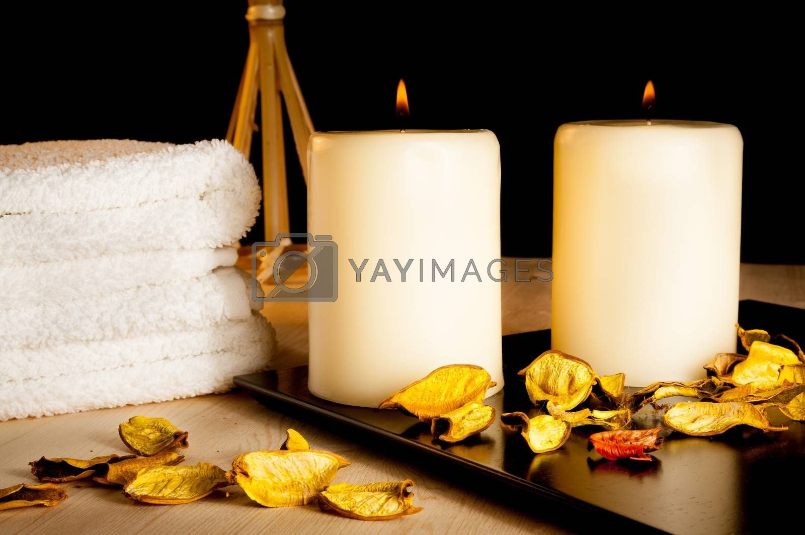 Spa massage border background with towel stacked, perfumed leaves and candles by donfiore