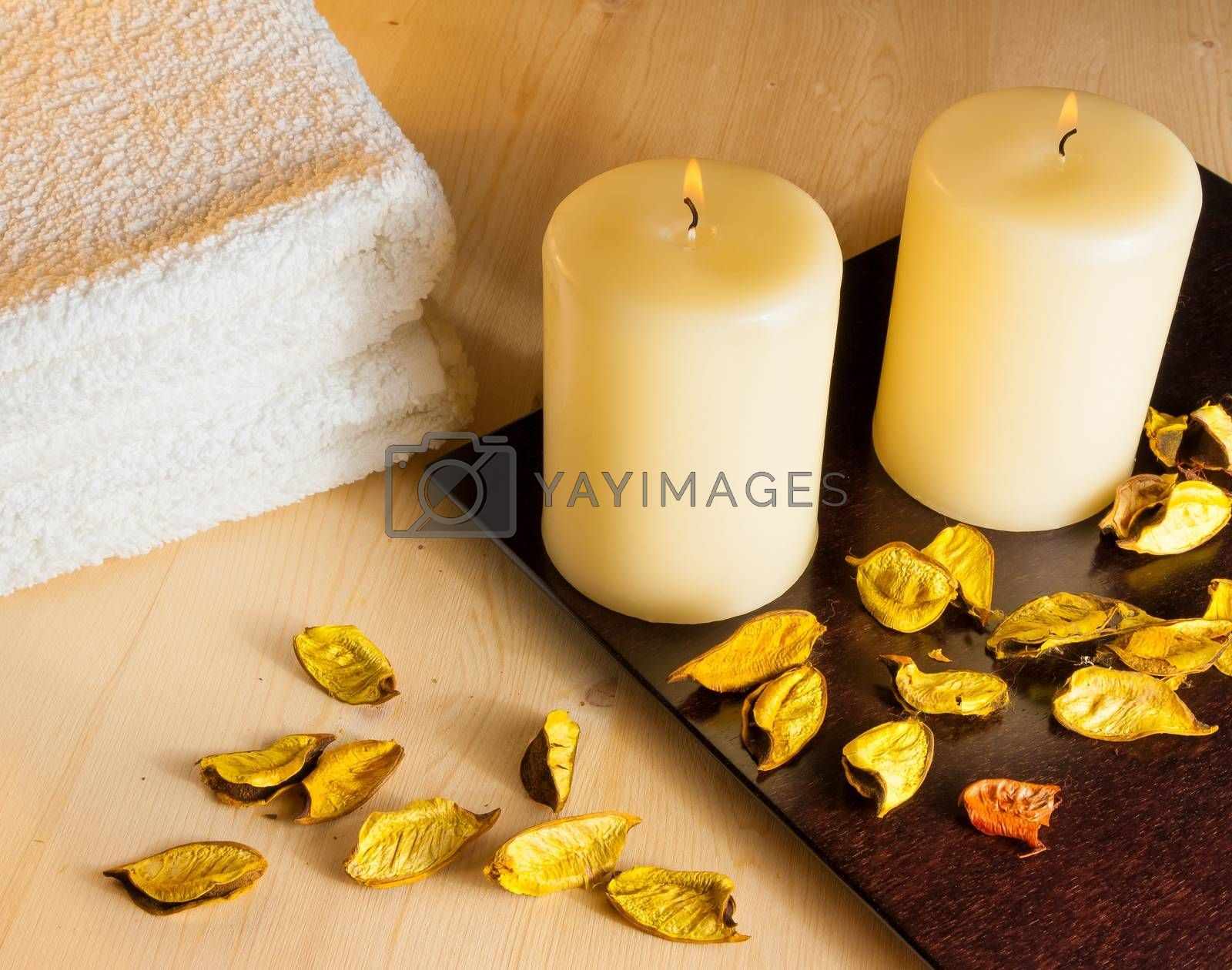 Top of view of spa massage border background with towel stacked, perfumed leaves, candles and sea salt by donfiore