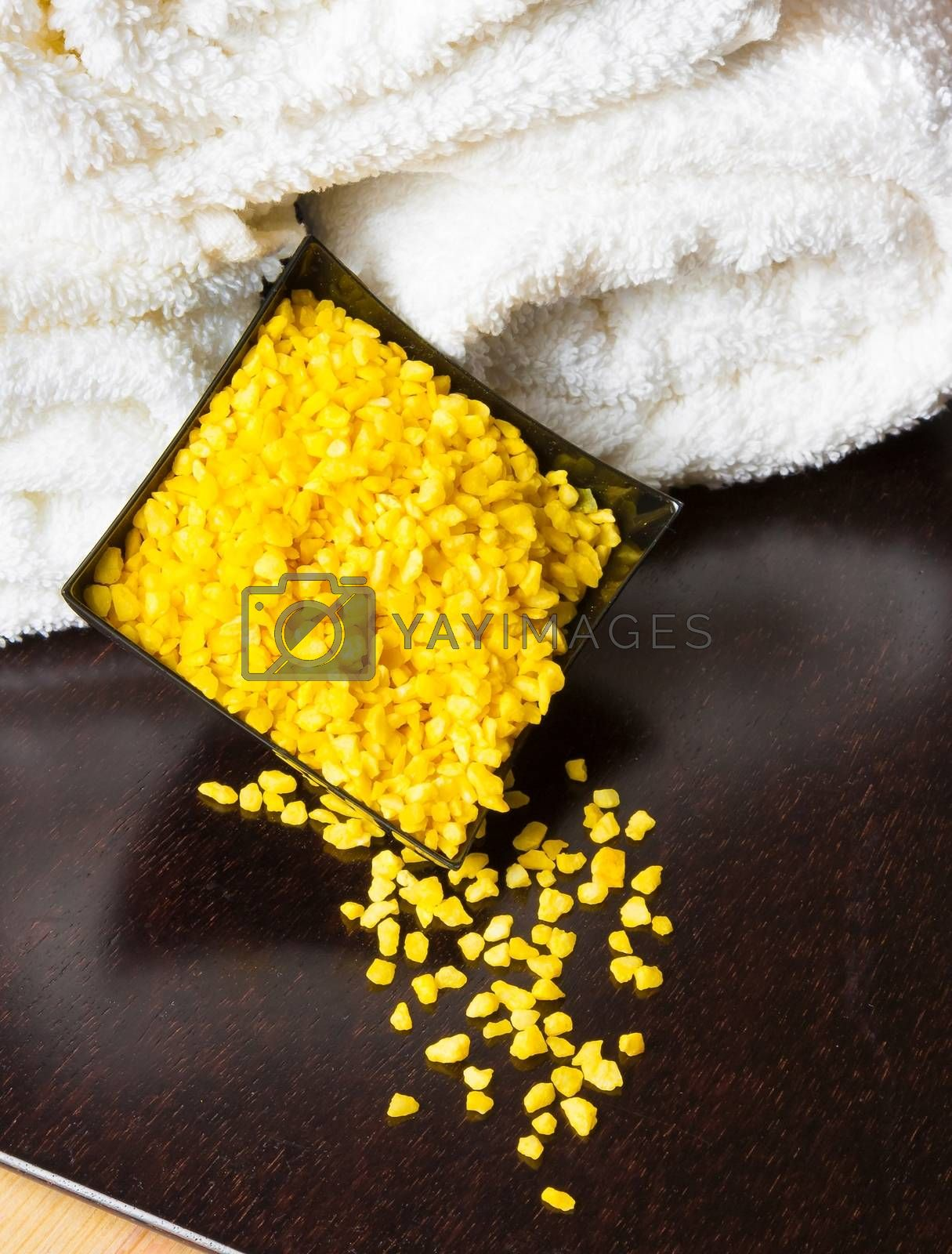 Spa massage border background with towel stacked and yellow sea salt by donfiore
