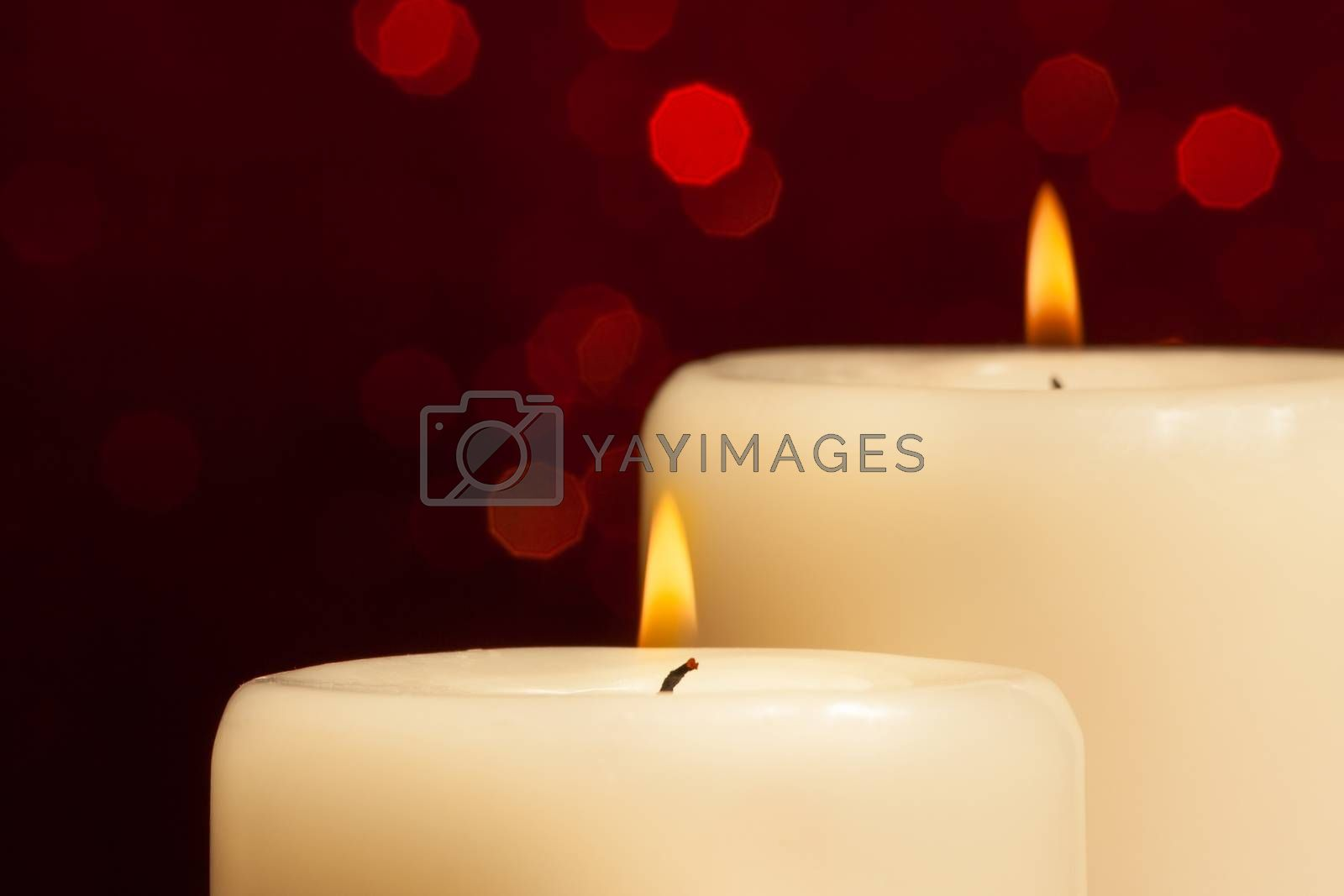 close-up of candles with flame on red bokeh by donfiore