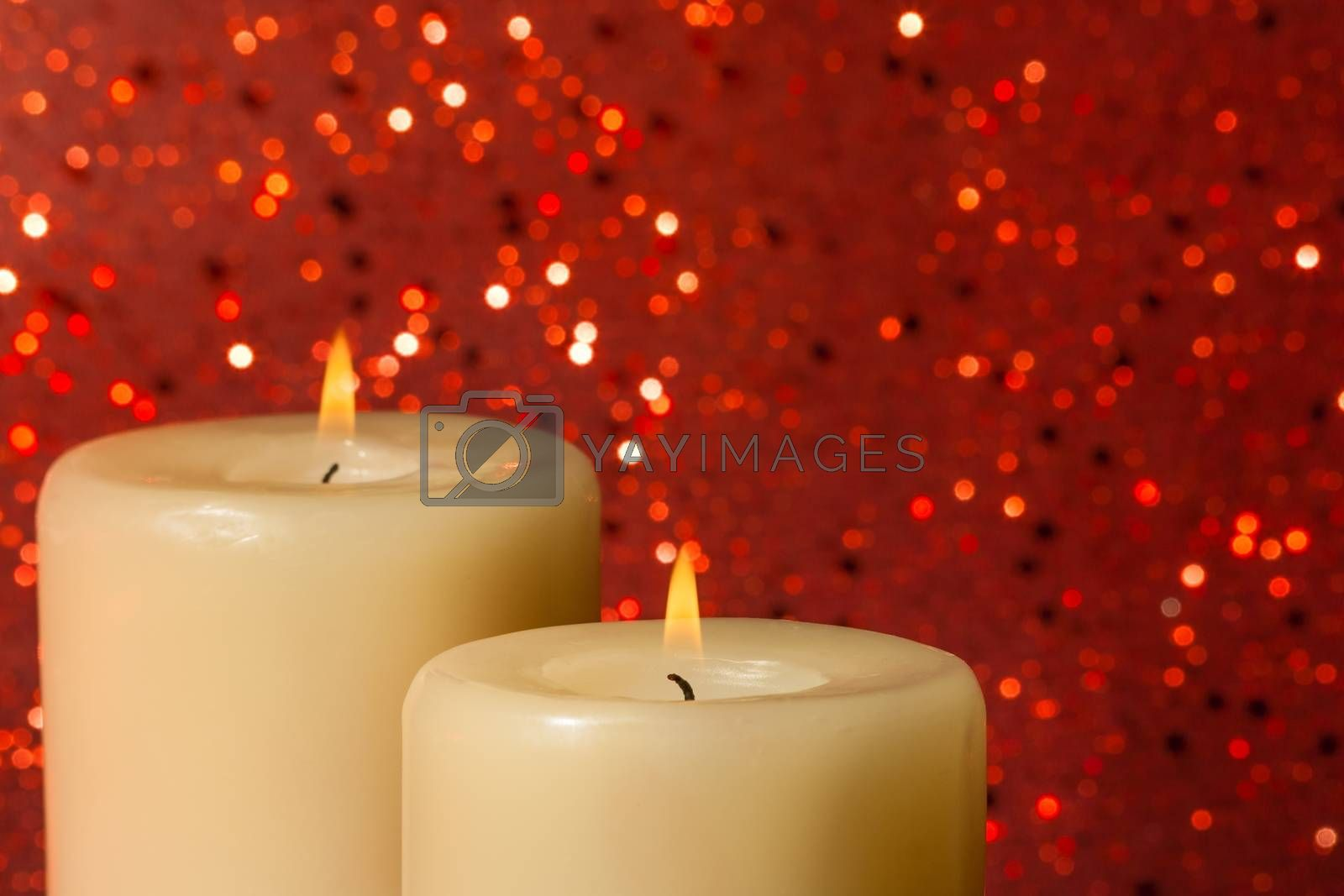 candles with flame on red bokeh by donfiore