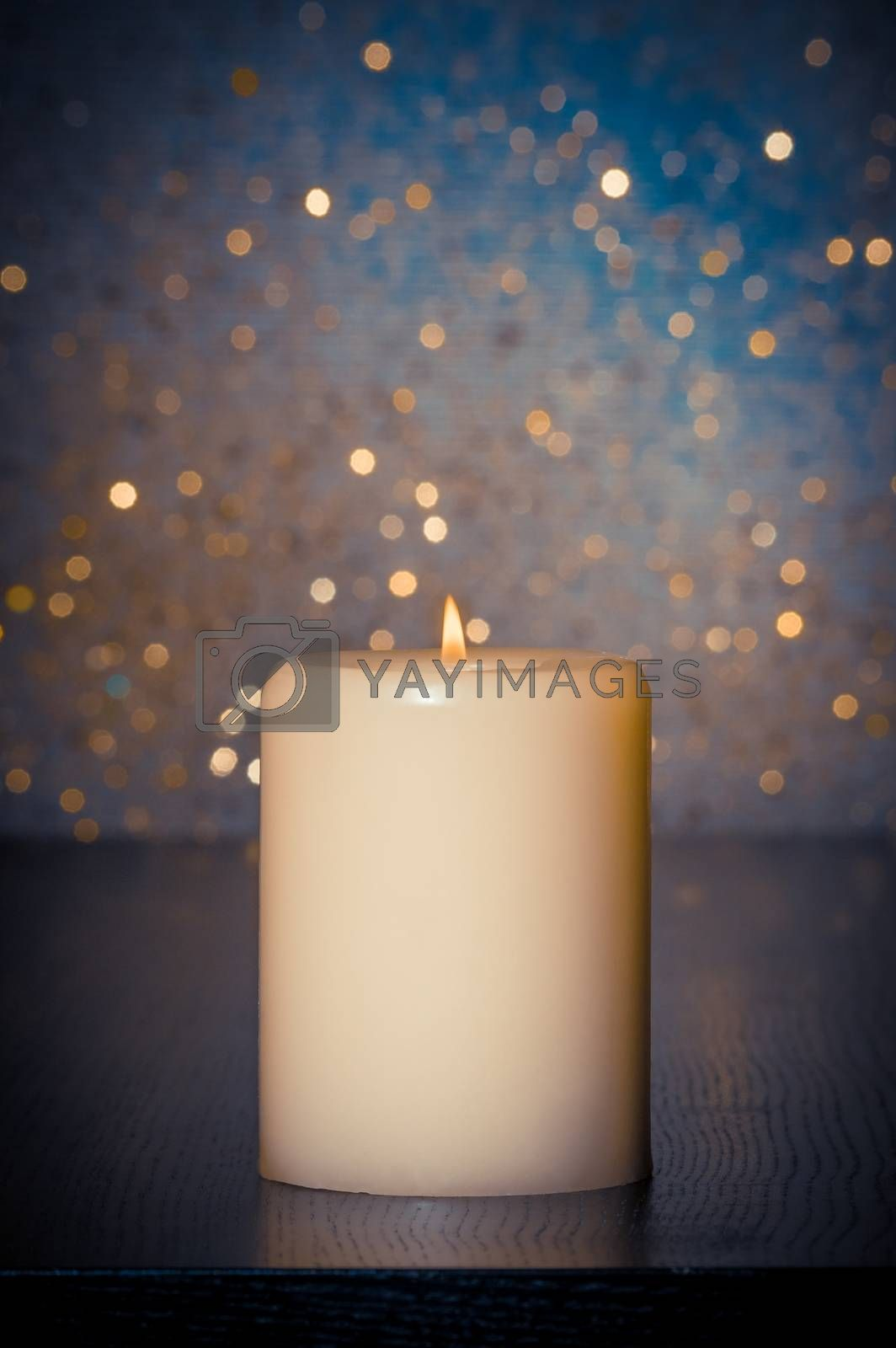 candle with flame on wood table on blue bokeh background by donfiore