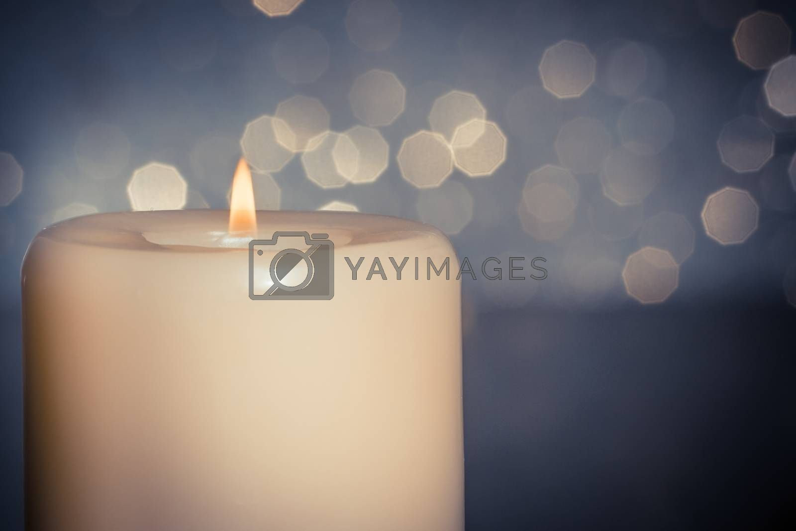 close-up of candle with flame on wood table on blue bokeh background by donfiore