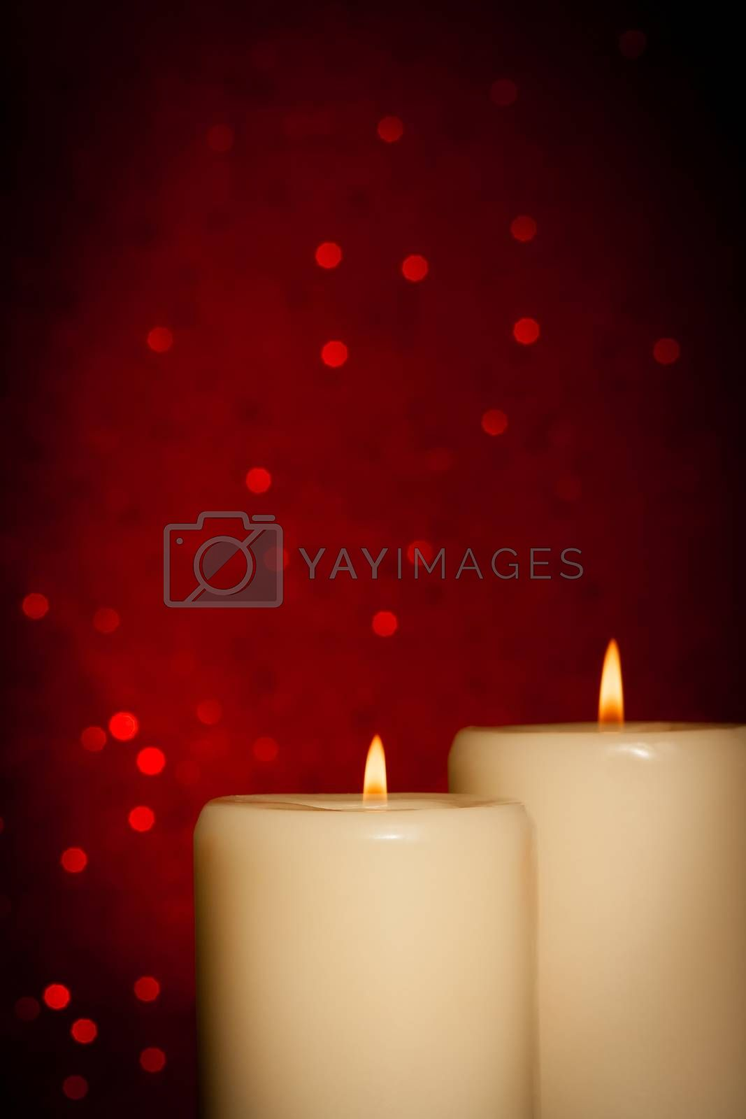 candles with flame and space for text on red bokeh by donfiore