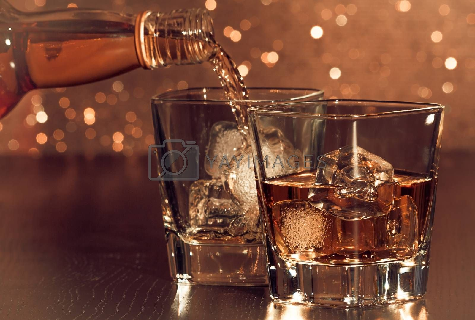 barman pouring whiskey behind whiskey glass by donfiore