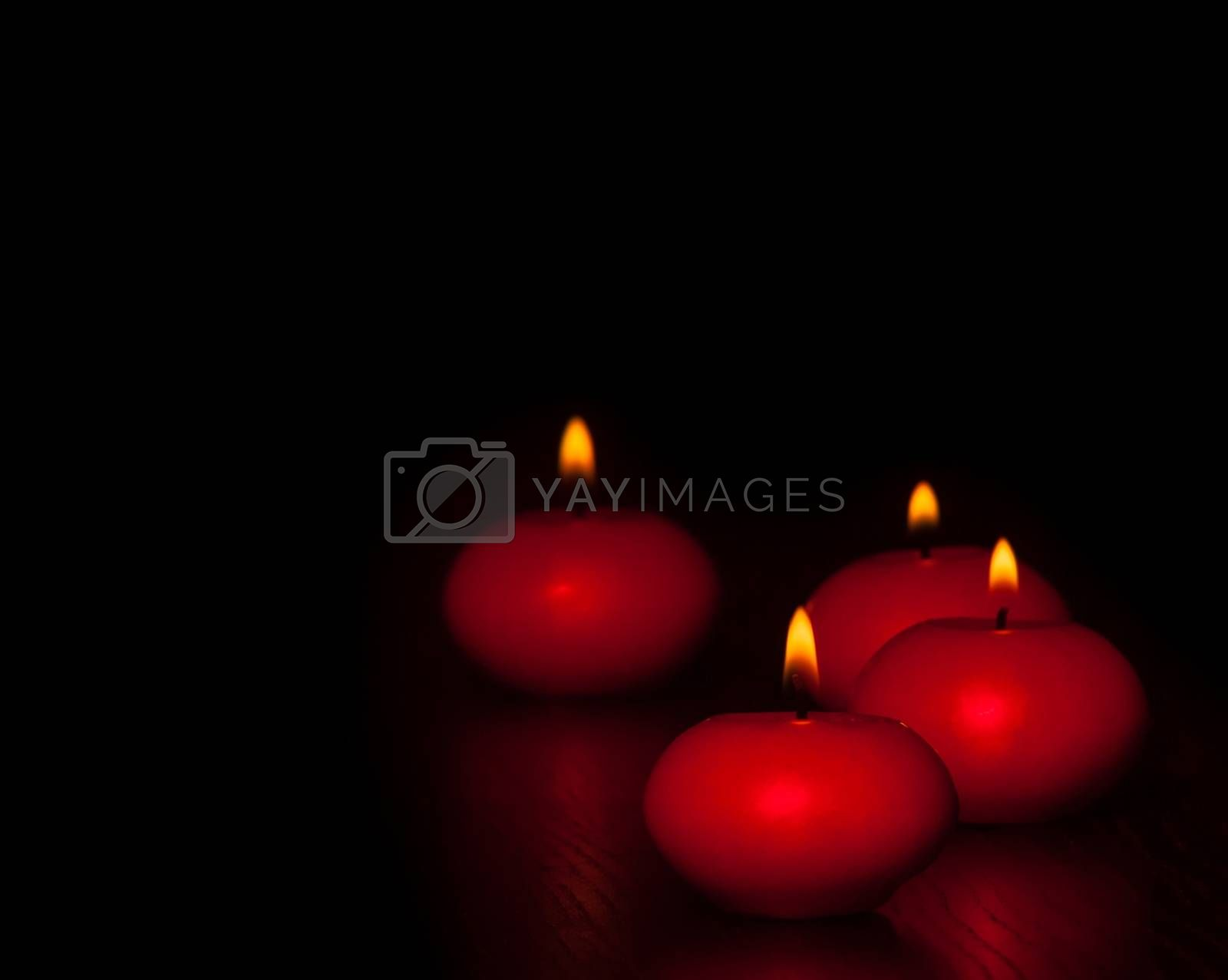 red candles with flame on wood and black background, dark atmospere by donfiore