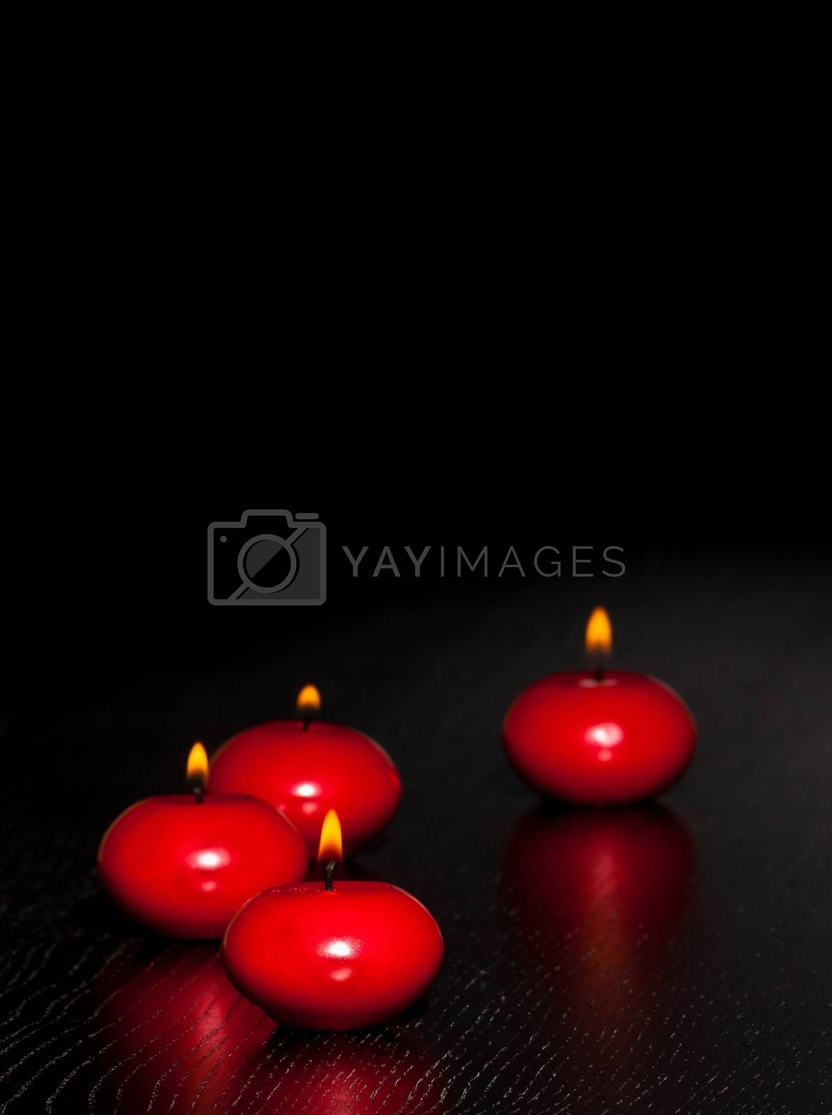 red candles with flame on wood and black background  by donfiore