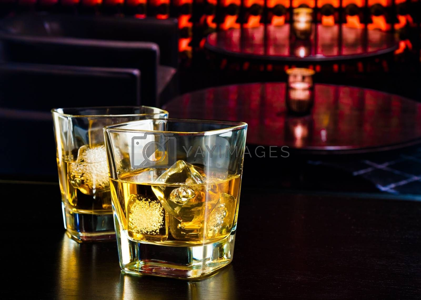 whiskey glasses with ice in a lounge bar by donfiore