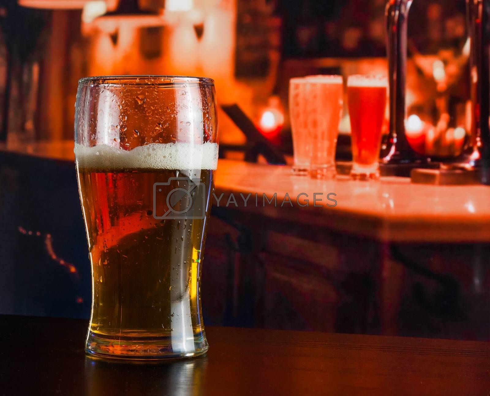 Glass of fresh beer on wood table  by donfiore