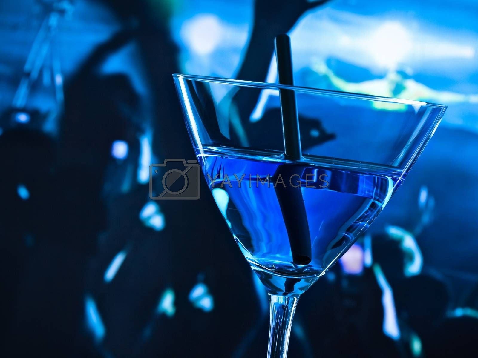 detail of blue cocktail drink on a disco table with space for text by donfiore