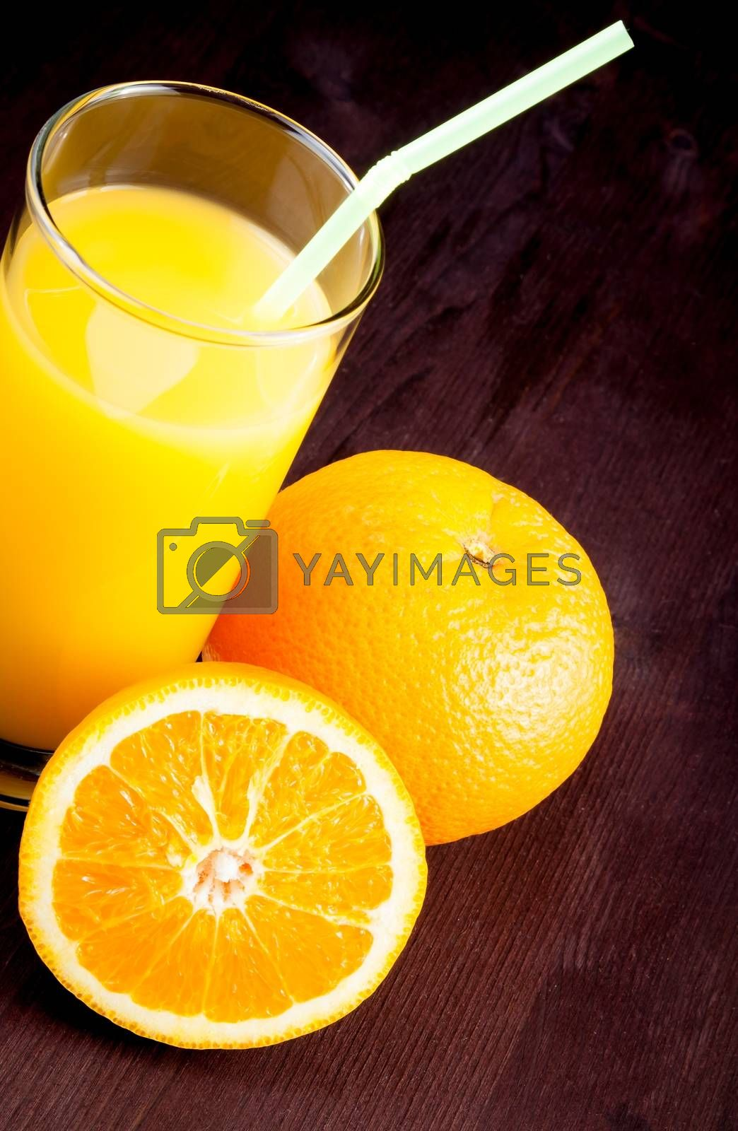 top of view of full glass of orange juice with straw near fruit orange by donfiore