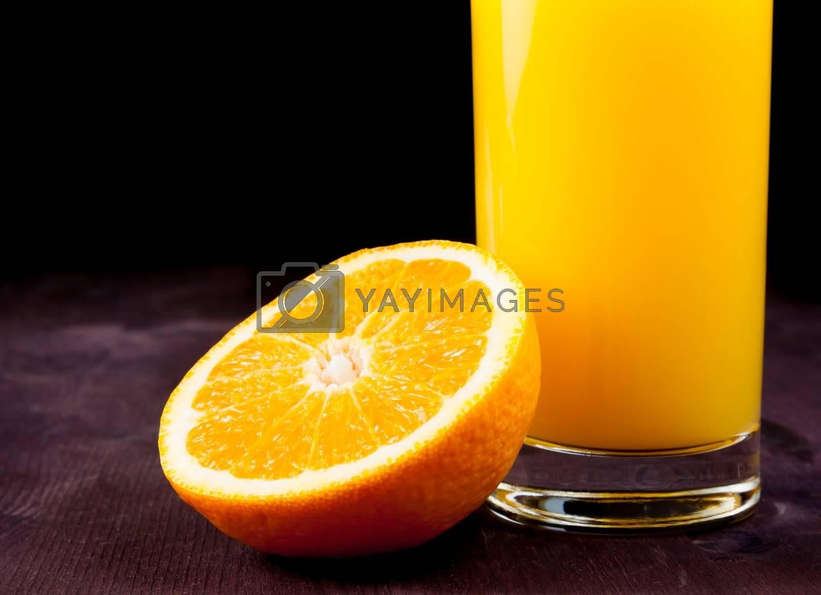 detail of full glass of orange juice near half orange by donfiore