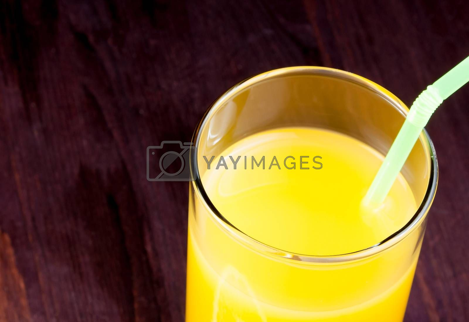 top of view of full glass of orange juice with straw with space for text by donfiore