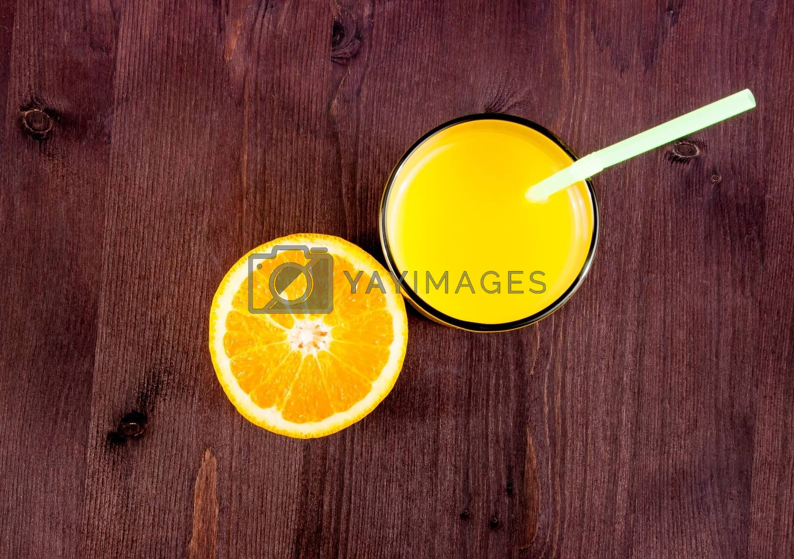 top of view of full glass of orange juice with straw and half orange with space for text by donfiore