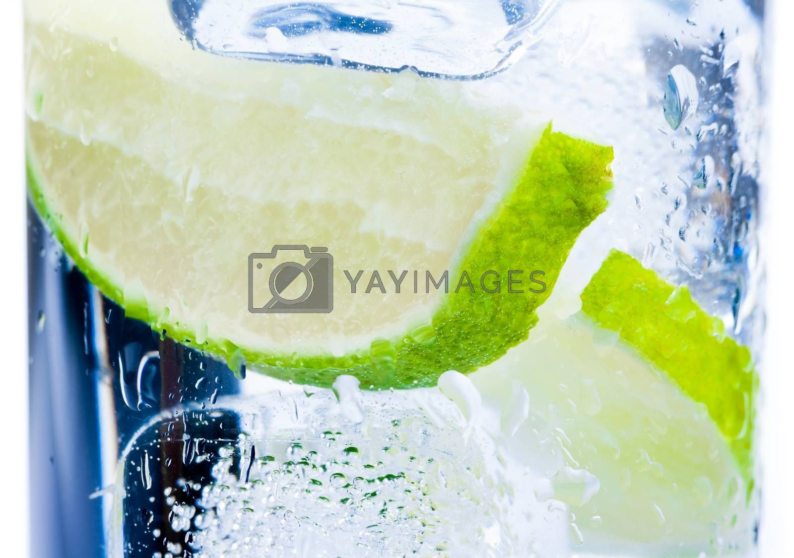 close-up of cocktail glass with ice and lime slice isolated by donfiore