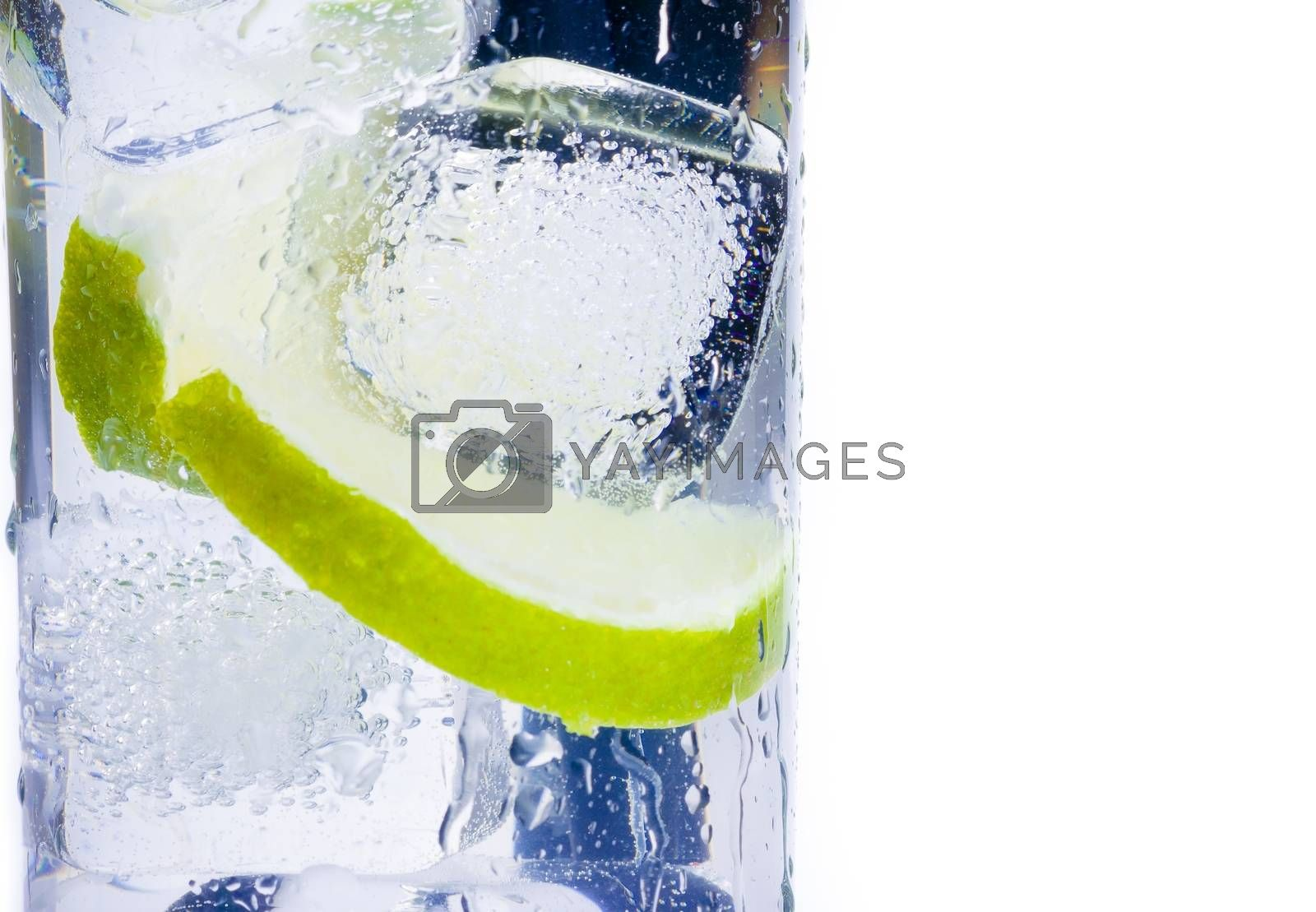 close-up of cocktail glass with ice and lime slice isolated and space for text by donfiore