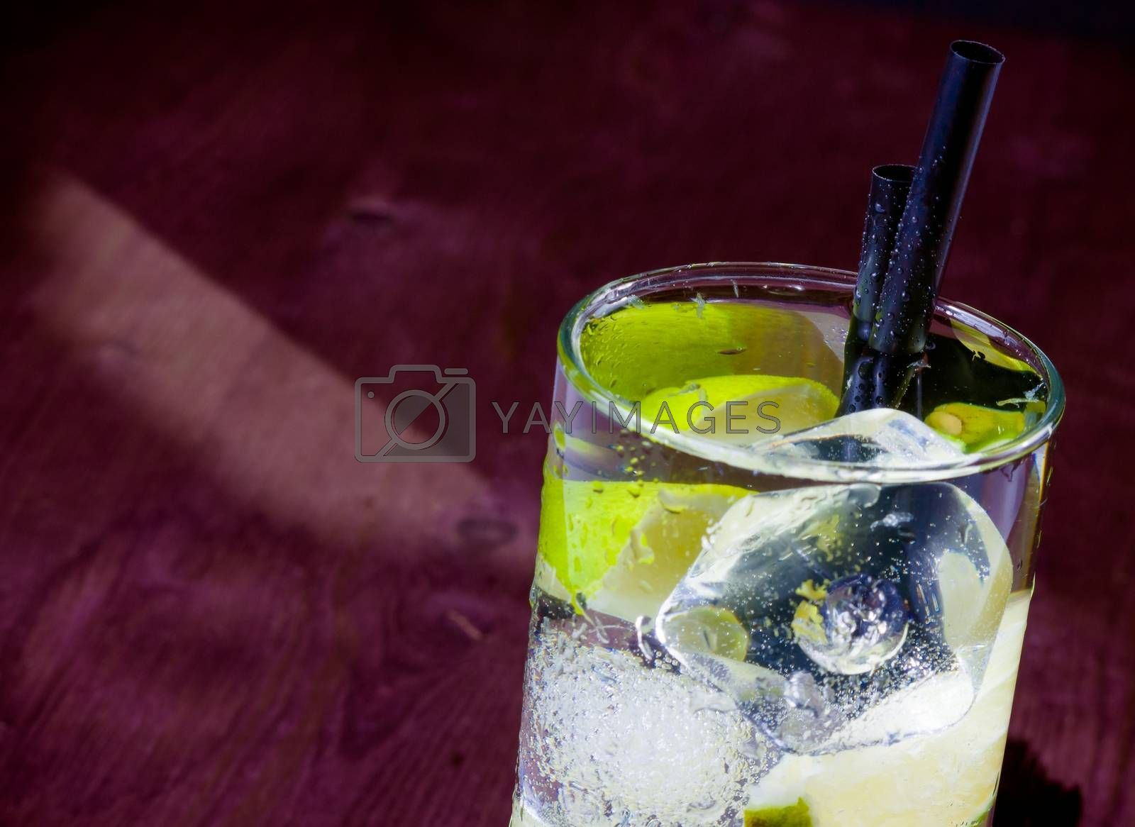Cocktail with ice and lime slice and space for text by donfiore