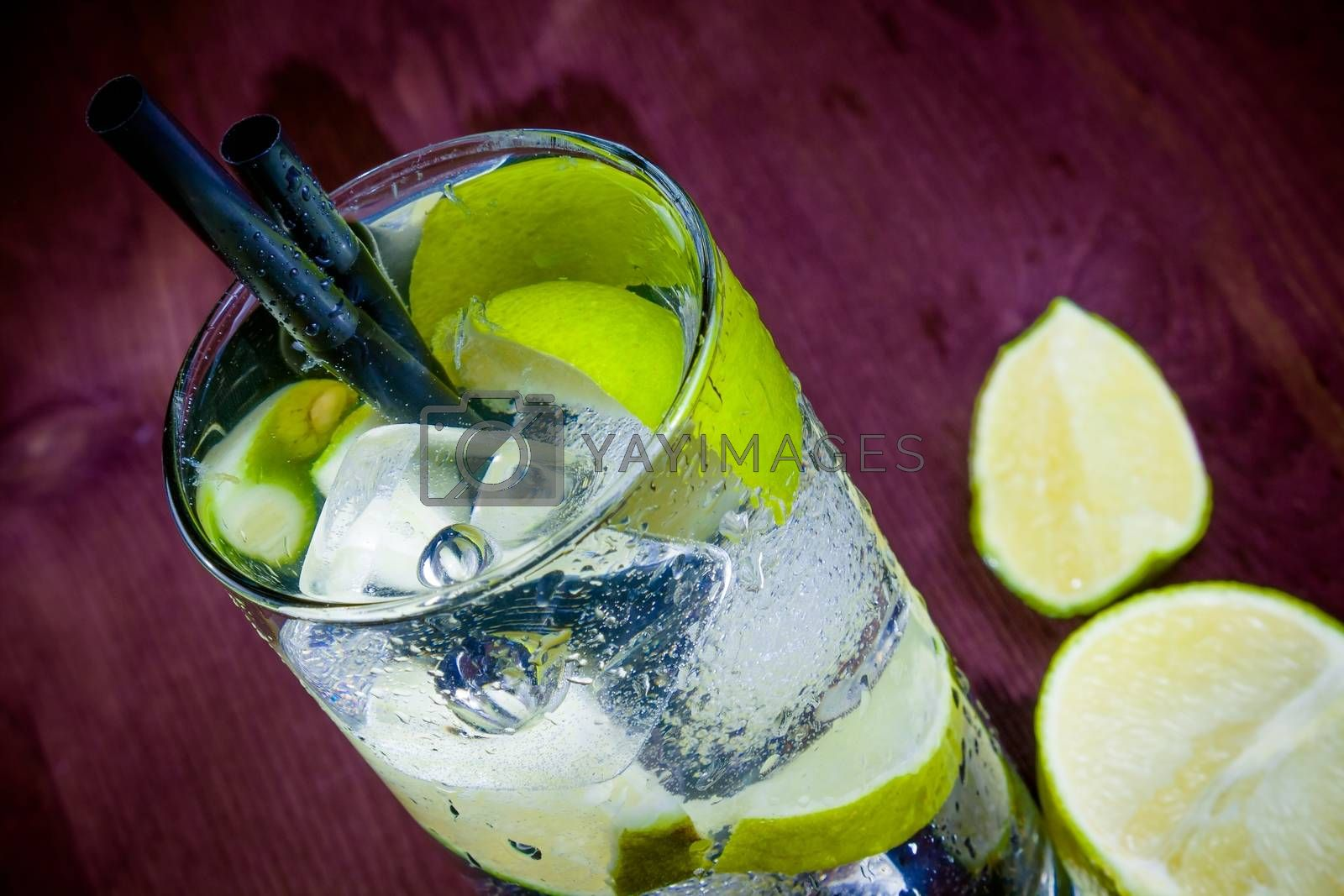 top of view of cocktail glass with ice and lime slice by donfiore