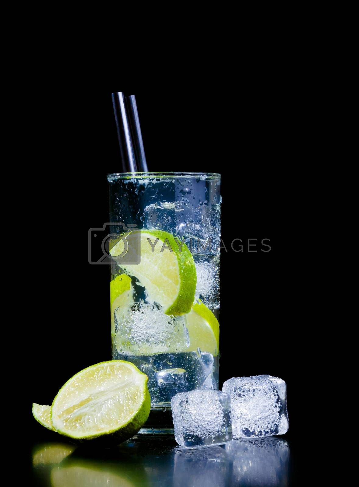 Cocktail with ice and lime slice with straw and space for text by donfiore