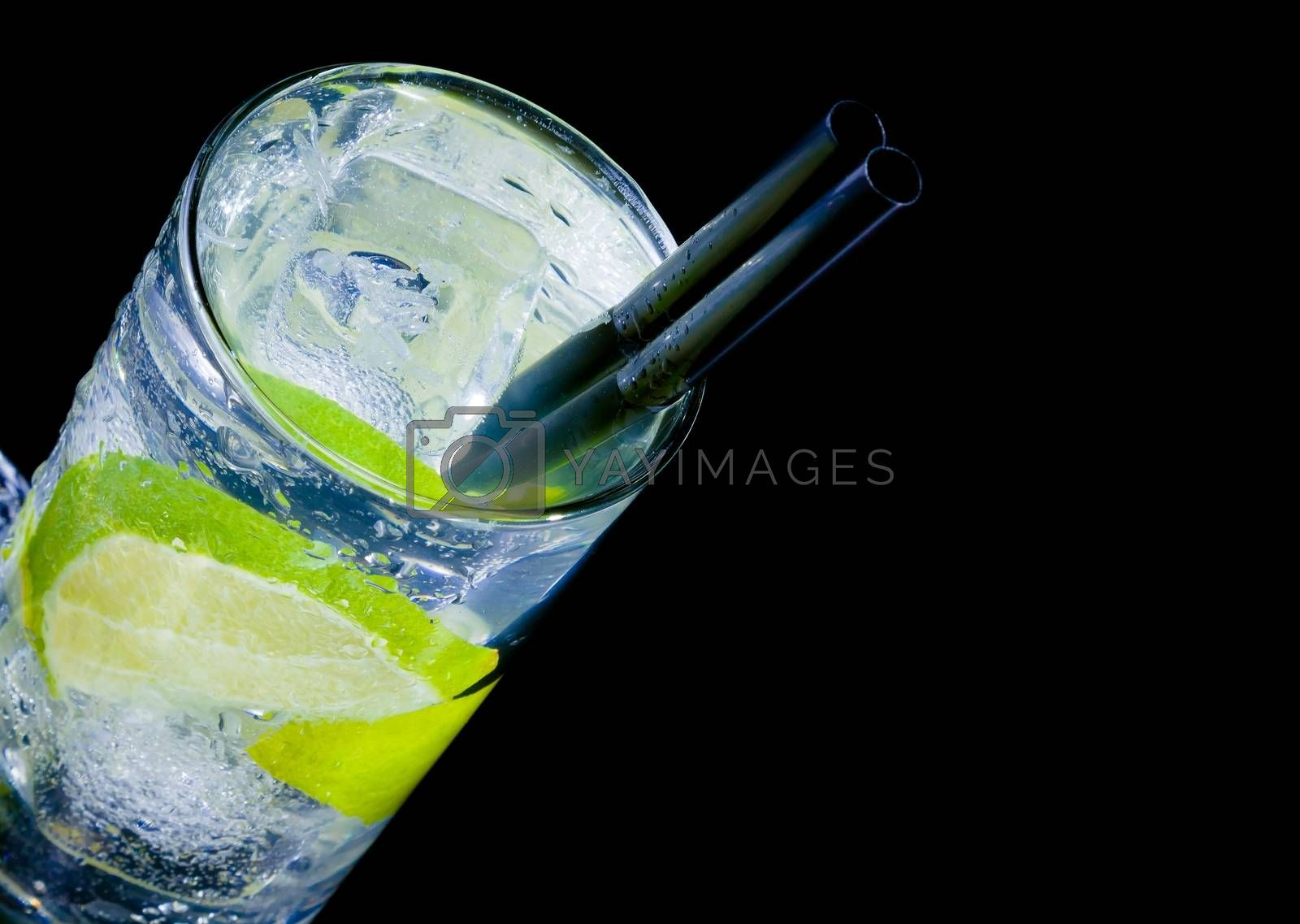 top of view of cocktail with ice and lime slice and space for text by donfiore