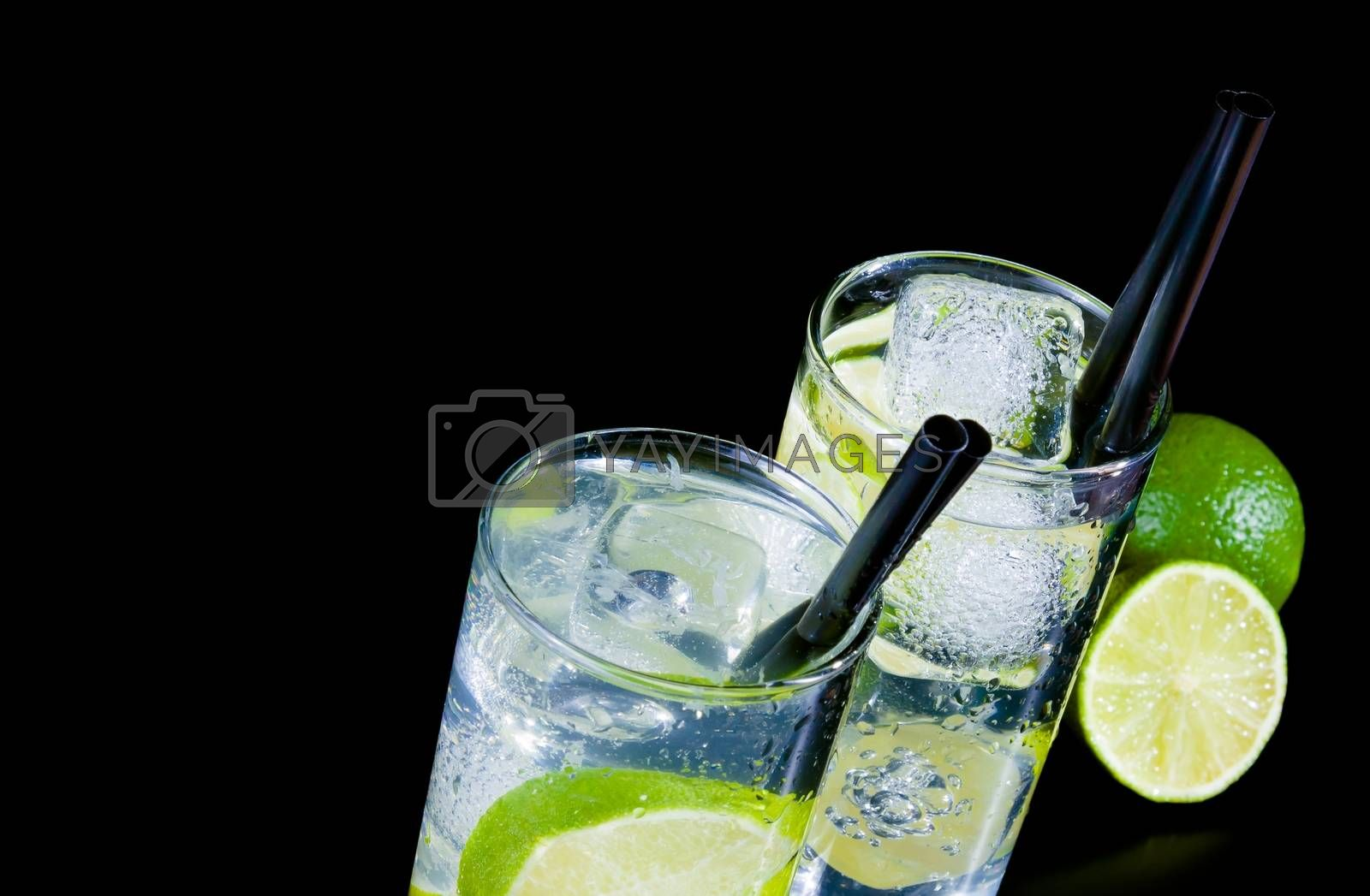 two glasses with cocktail and ice with lime slice on black table by donfiore
