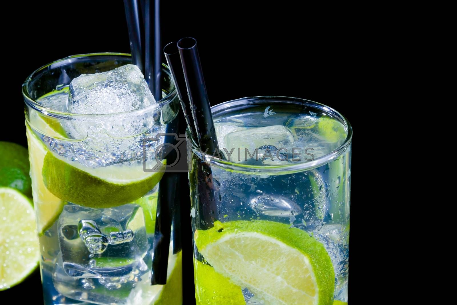 two glasses with cocktail and ice with lime slice on black background by donfiore