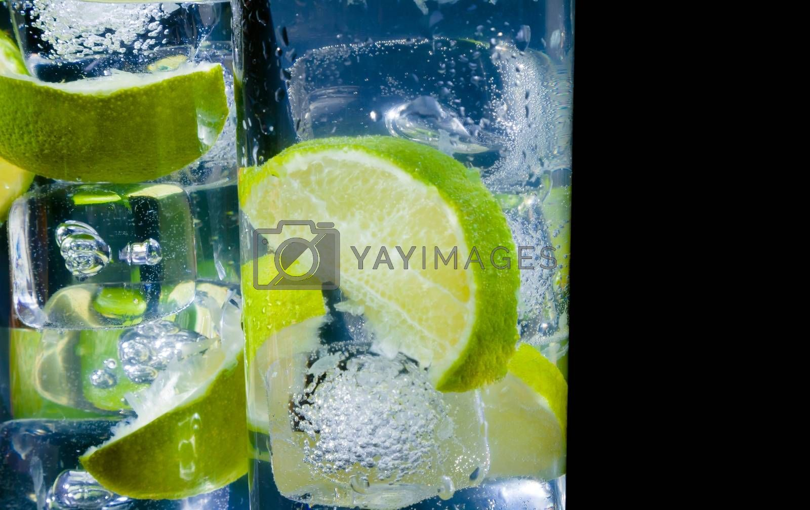 close-up of two glasses with cocktail and ice with lime slice on black background with space for text by donfiore