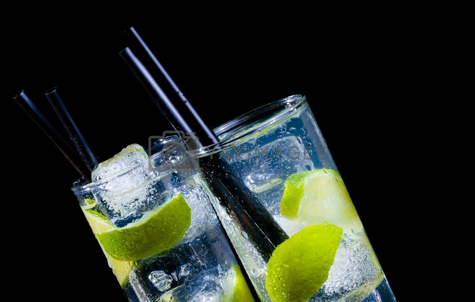 two glasses with cocktail and ice with lime slice on black background with space for text by donfiore