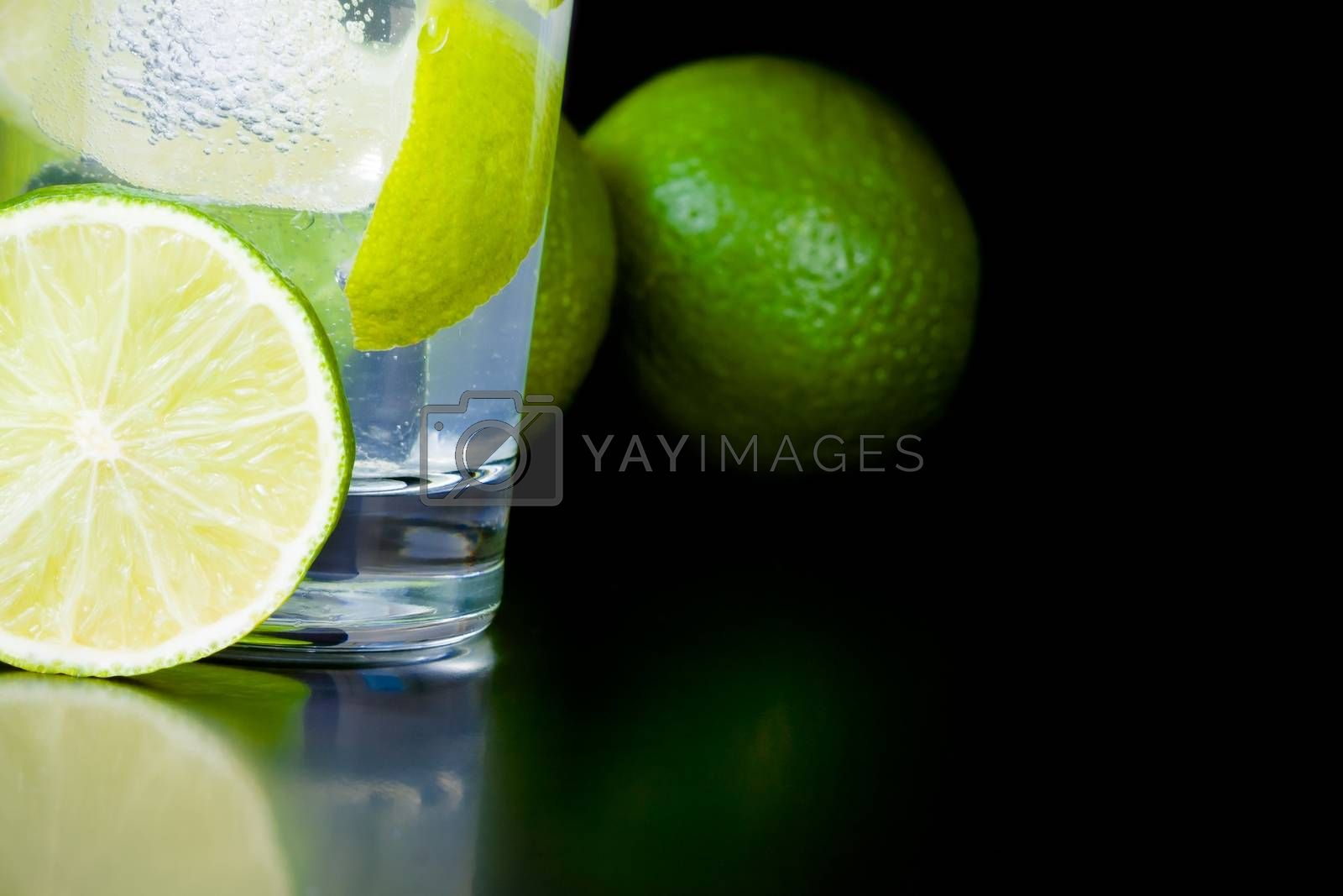 detail of lime slice near cocktail with ice and space for text by donfiore