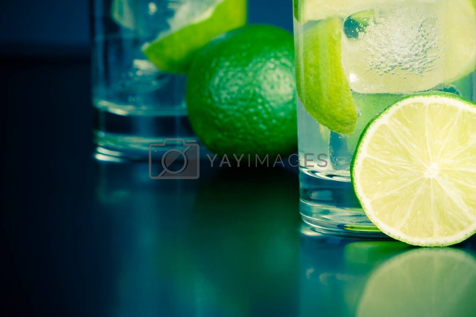 two glasses with cocktail and ice with lime slice on table by donfiore