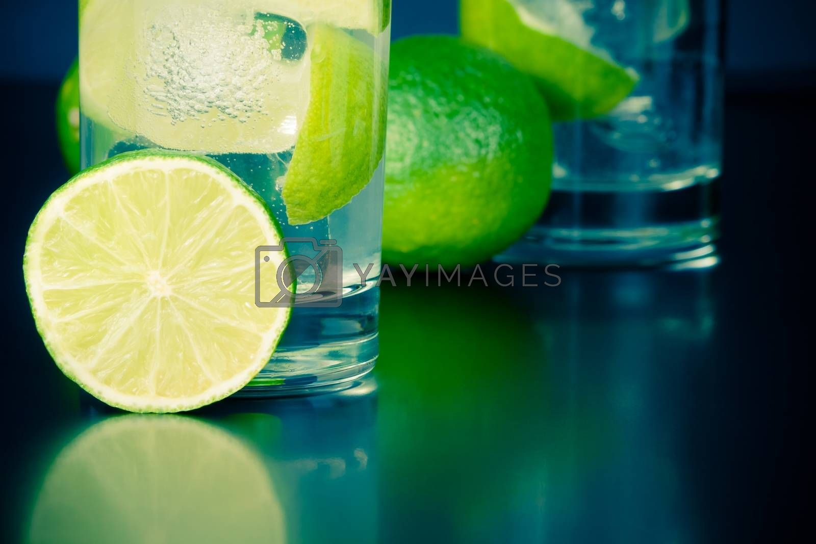 two glasses with cocktail and lime slice on table by donfiore