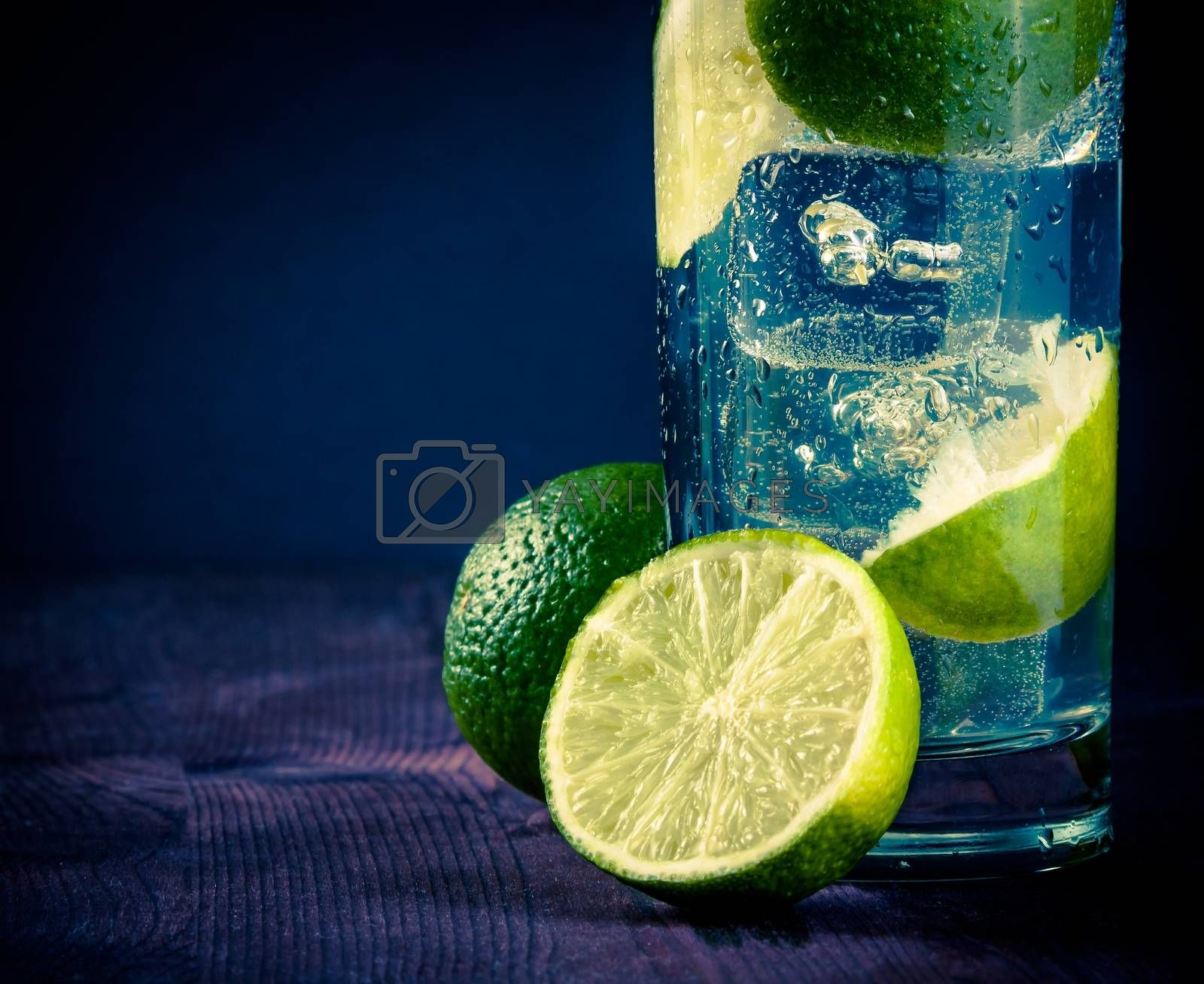 Cocktail with ice and lime slice and space for text, club atmosphere by donfiore