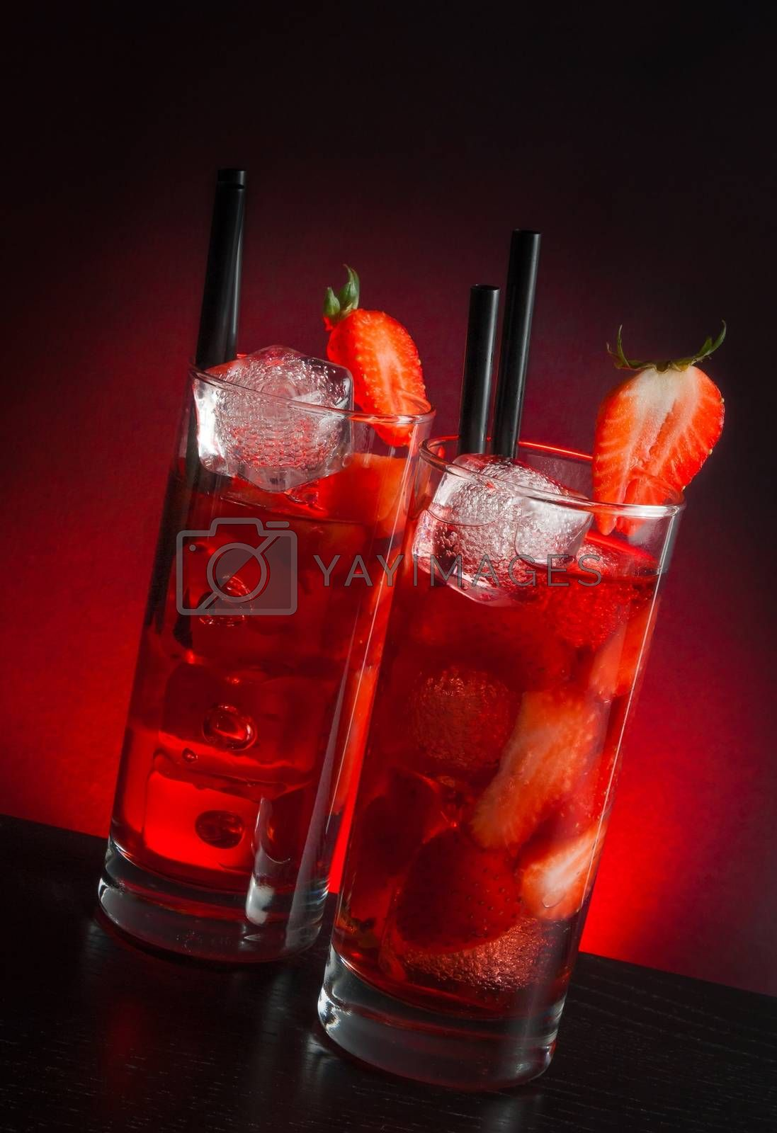 two glasses of strawberry cocktail with ice on wood table  by donfiore