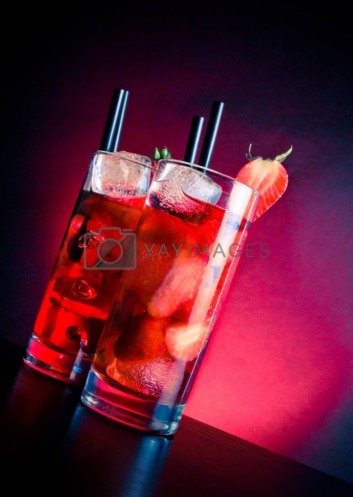 glasses of strawberry cocktail with ice on wood table by donfiore