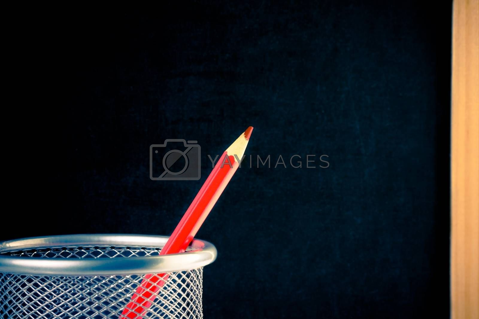 back to school, red pencil in container against empty blackboard for text