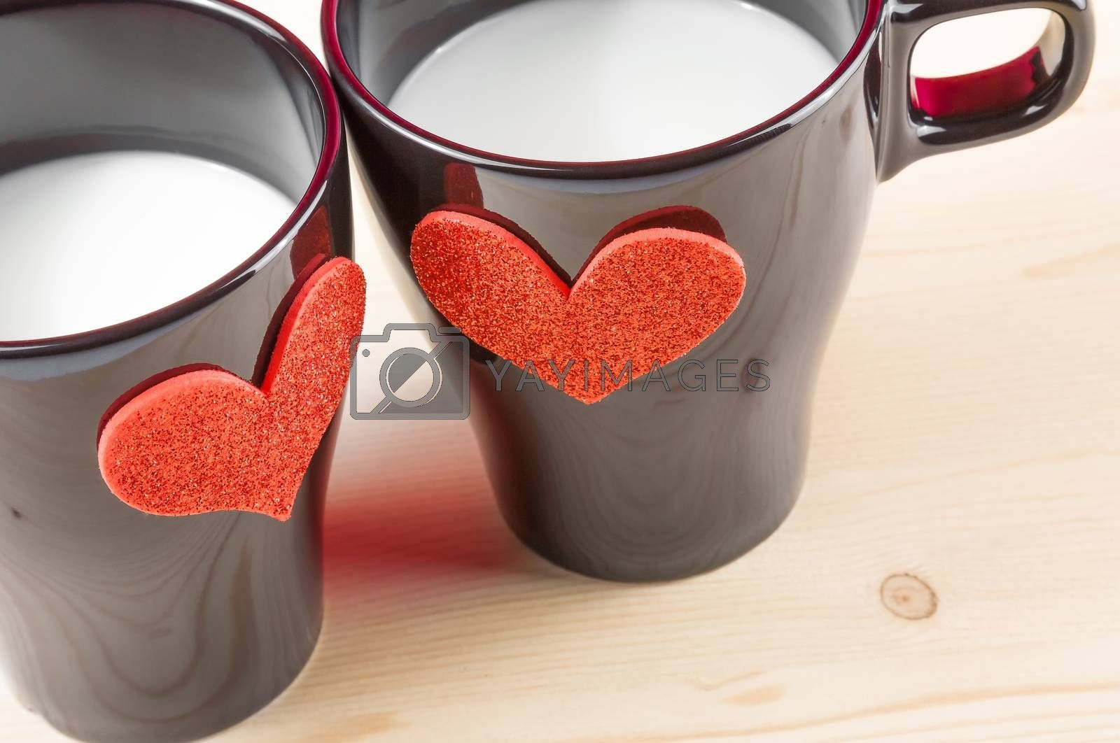 Royalty free image of cups of milk with decorative hearts on wood table, concept of valentine day by donfiore