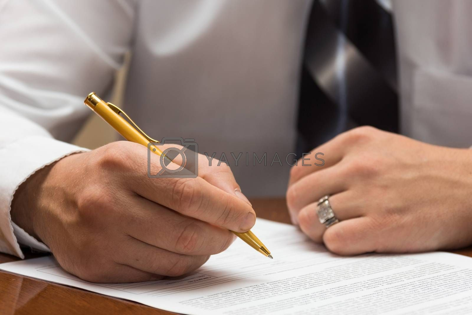 The photo depicts a man signs a document